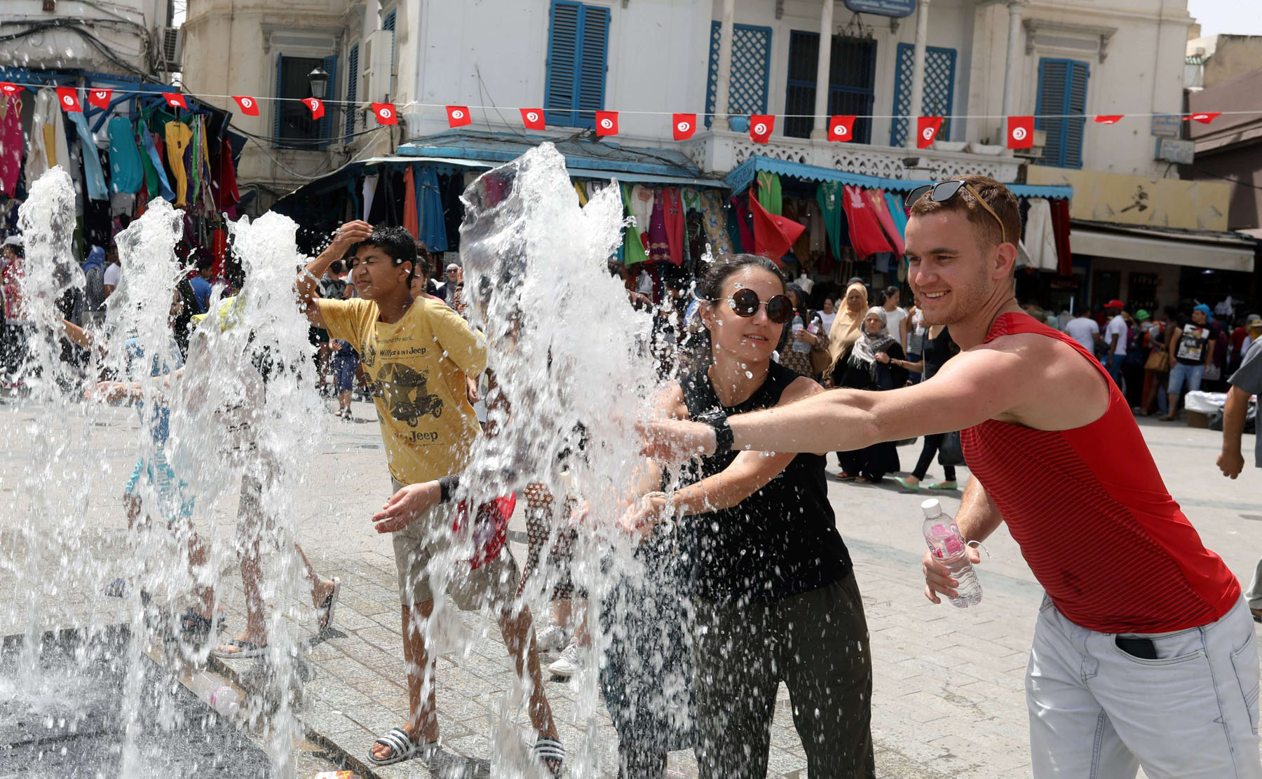 Precious commodity. People cool off at a water fountain on a hot day in Tunis.                                                                                          (Reuters)