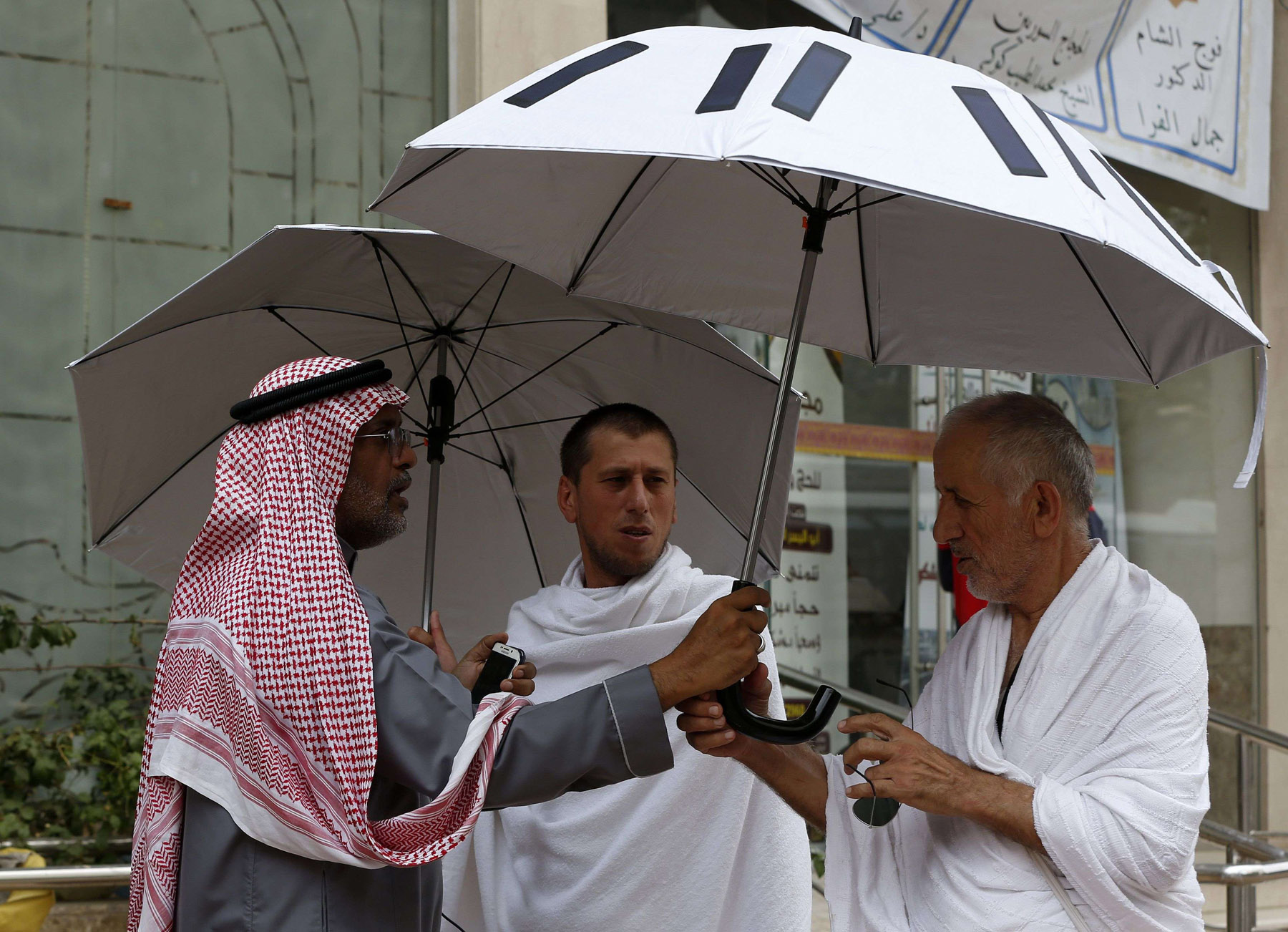 A Saudi engineer (L) shows pilgrims a smart umbrella, which uses solar energy to cool the user, in the Saudi holy city of Mecca. (AFP)