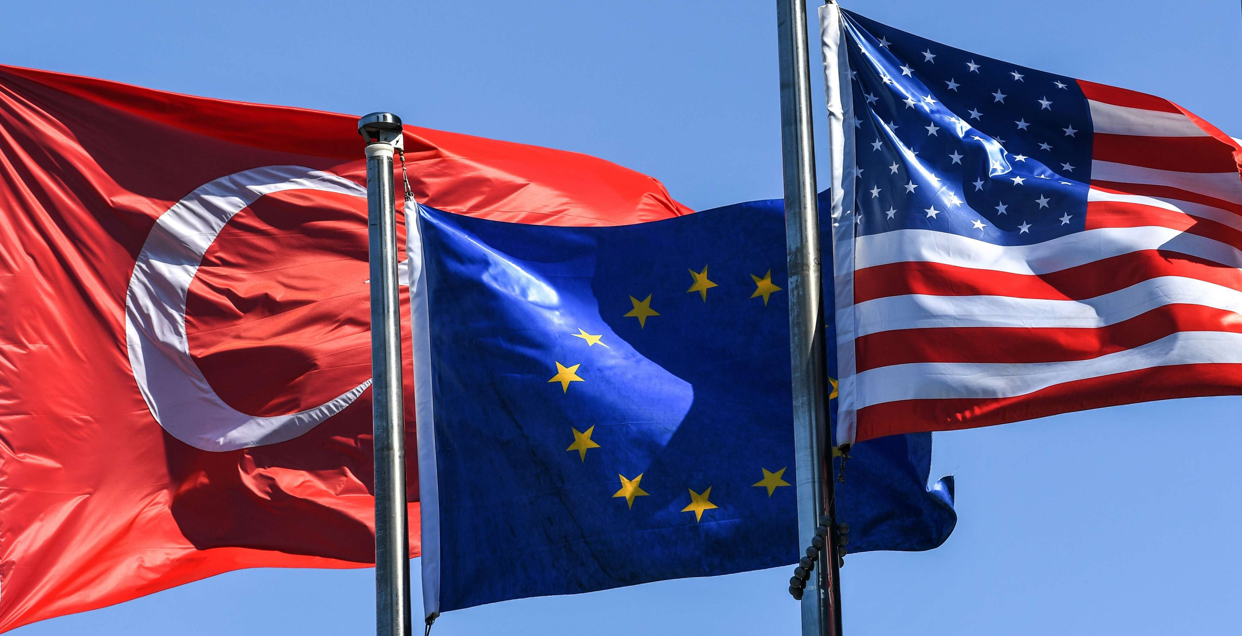 Turkish flag (L) European Union's flag (C) and US flag float at the financial and business district Maslak in Istanbul. (AFP)