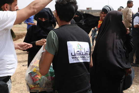 An Iraqi volunteer with the charity Wasel Tasel distributes food to displaced  raqis in Mosul. (Wasel Tasel)