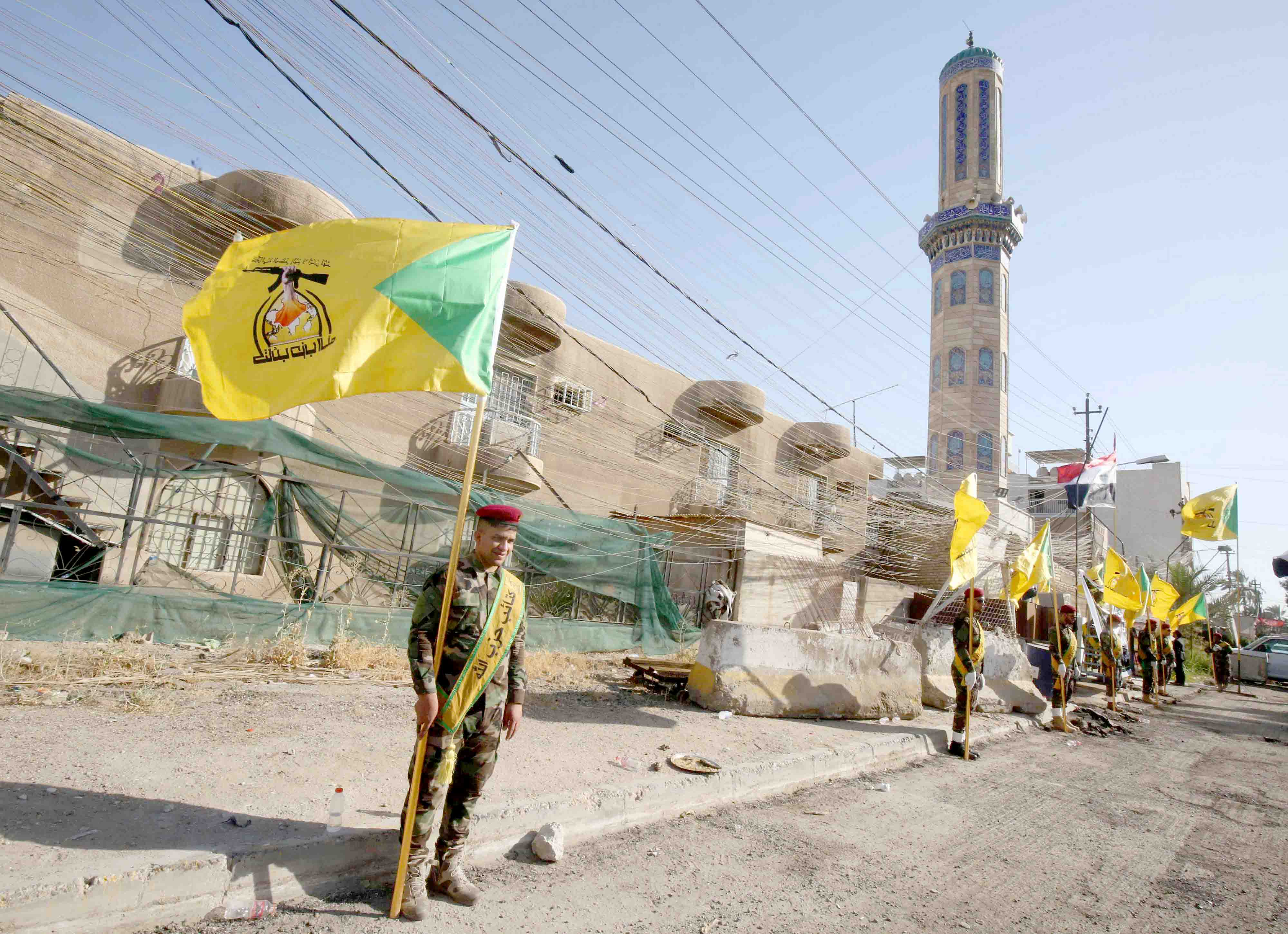 Growing network. Members of the Iran-backed Iraqi Hezbollah Brigades carry flags during a ceremony in Baghdad, last June. (AFP)