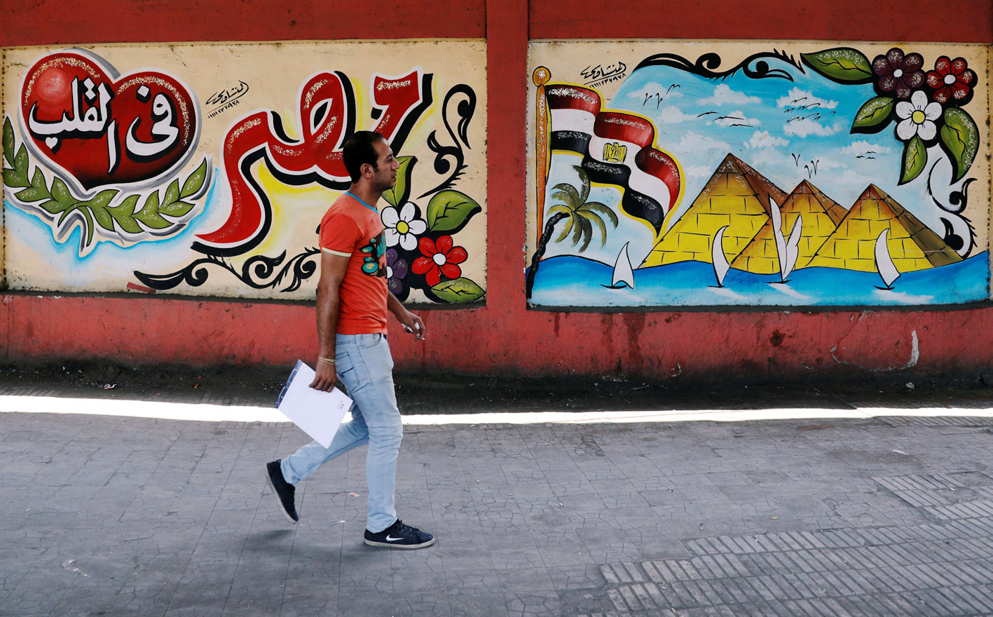 "A man in Cairo passes a mural that reads ""Egypt deep in our hearts."" (Reuters)"