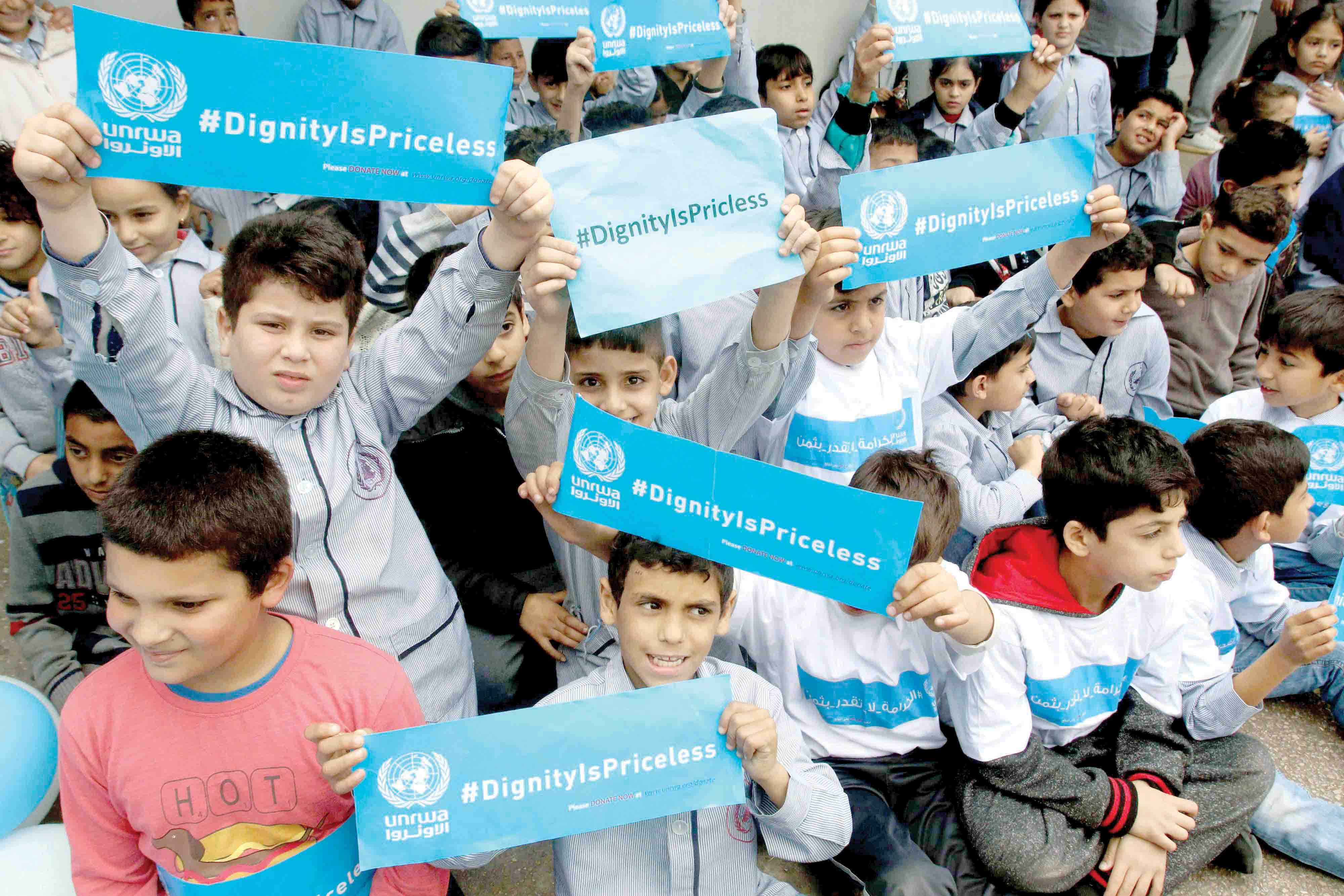 Palestinian refugee children hold placards at a school belonging to UNRWA in the Lebanese town of Sebline during a protest against US aid cuts to the organisation. (AFP)