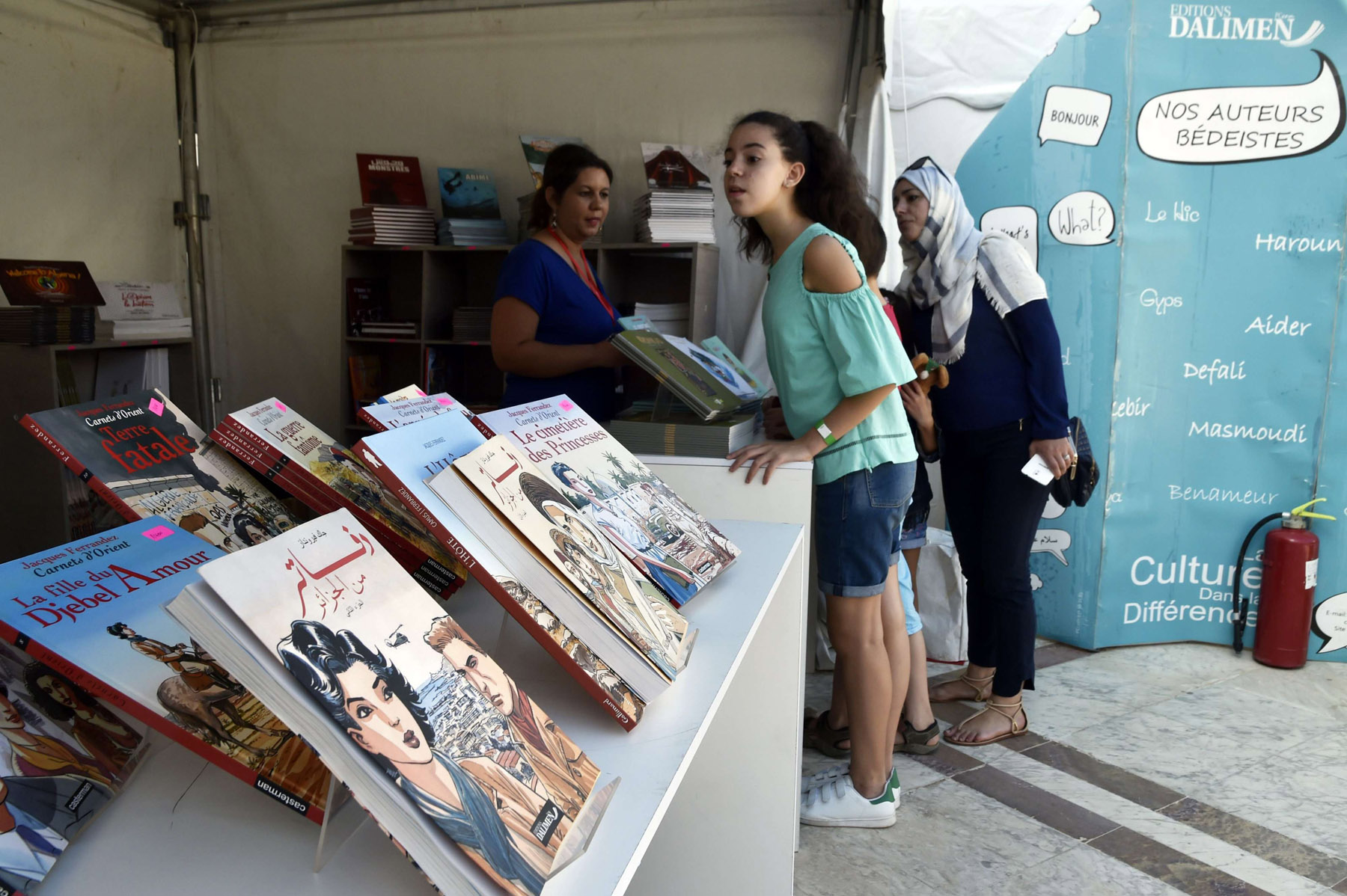 Under renewed threat. Algerian girls looks at graphic novels on display during the 10th Algiers  International Comic Festival, last October.   (AFP)