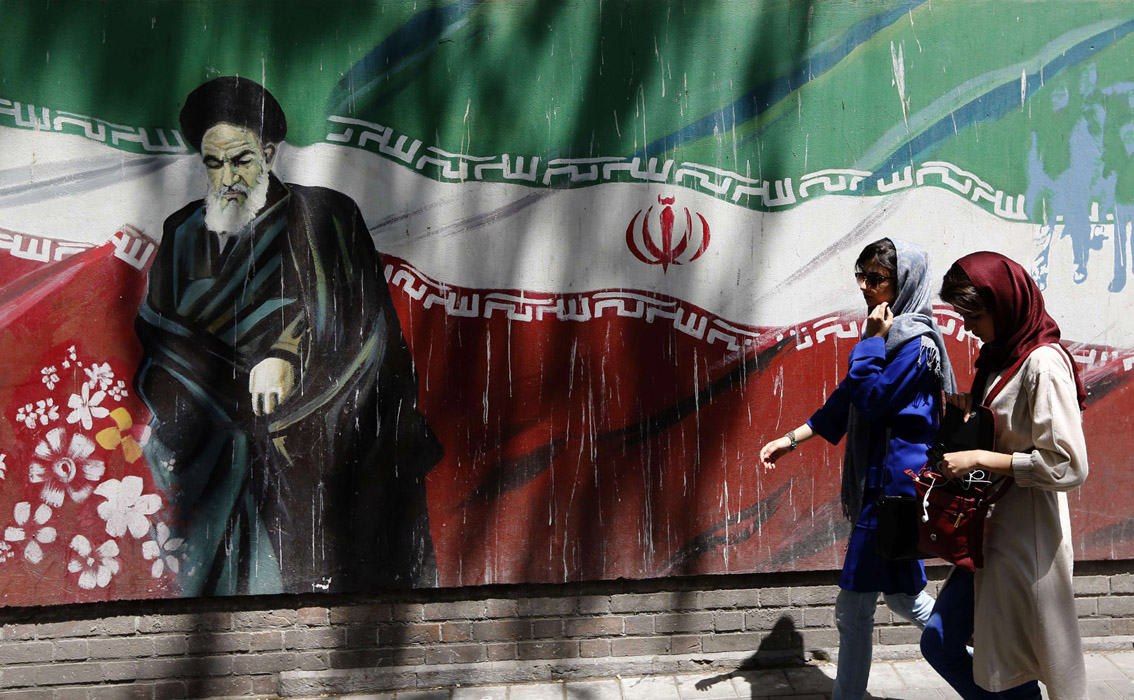 Iranians walk by a mural painting of the founder of the Islamic Republic  Ayatollah Ruhollah Khomeini on the wall of the former US Embassy in Tehran. (AFP)