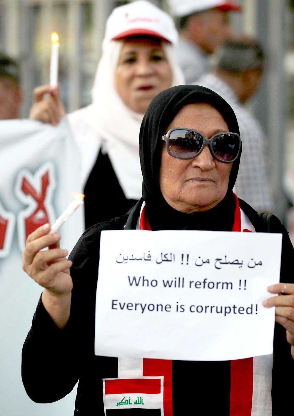 Stubborn problem. An Iraqi woman holds a sign and a candle during a demonstration in Baghdad's Tahrir Square, on July 31. (AFP)