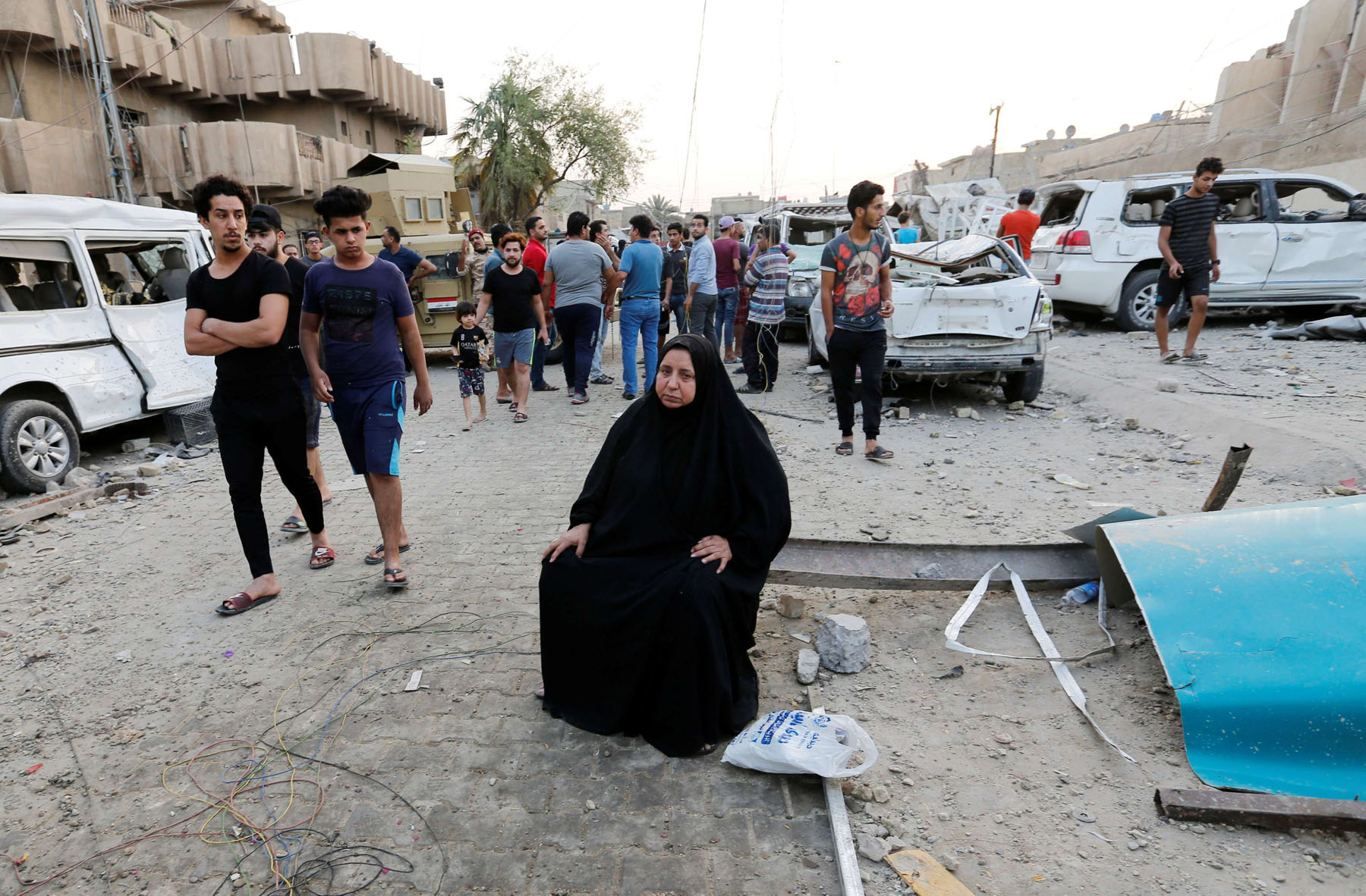 A woman sits near the scene of an explosion in Baghdad's Sadr City district, last June. (Reuters)