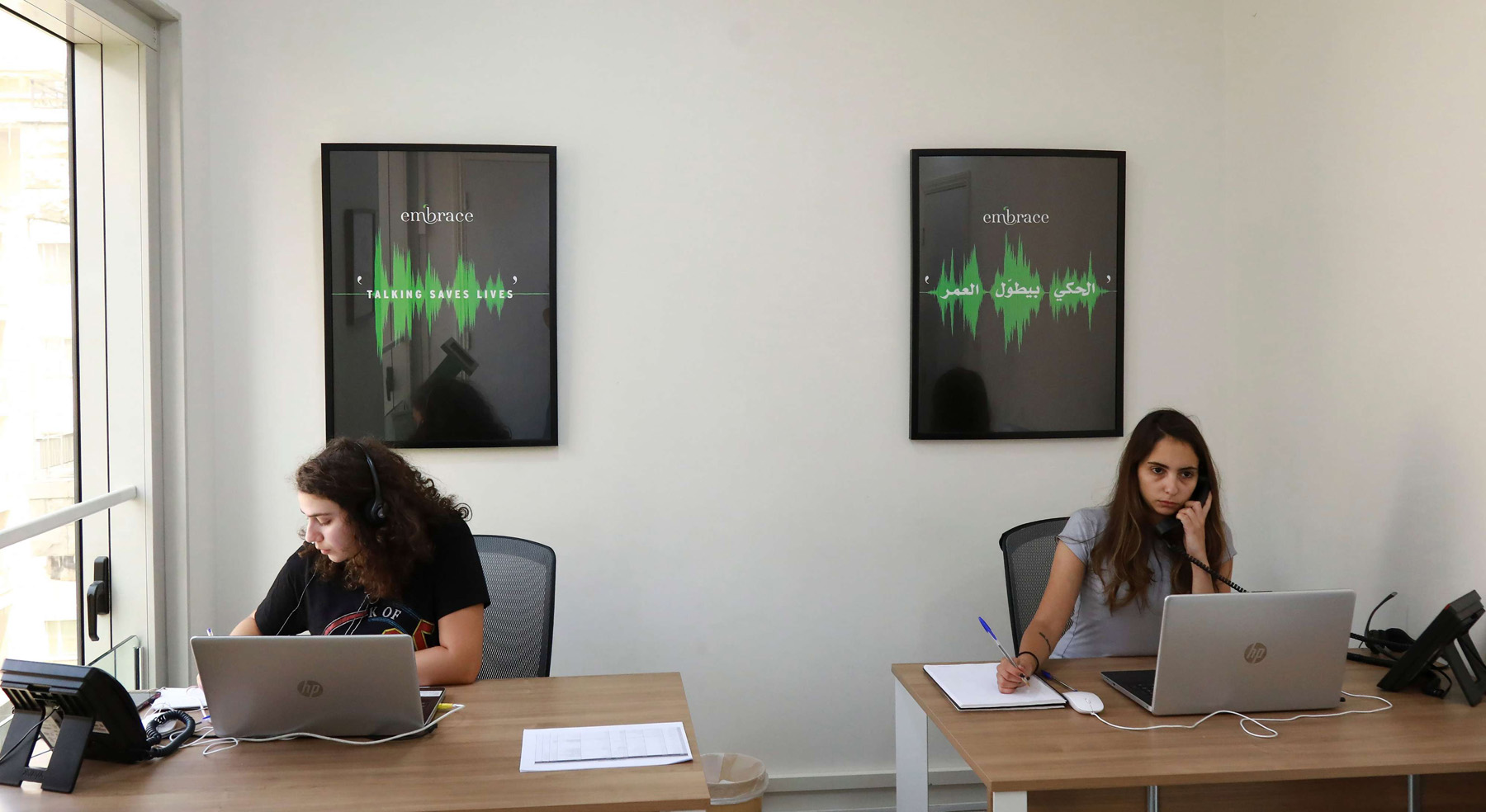 Sally (L) and Serene listen to callers at Embrace, a suicide prevention helpline, in the Lebanese capital Beirut on July 13, 2018. (AFP)