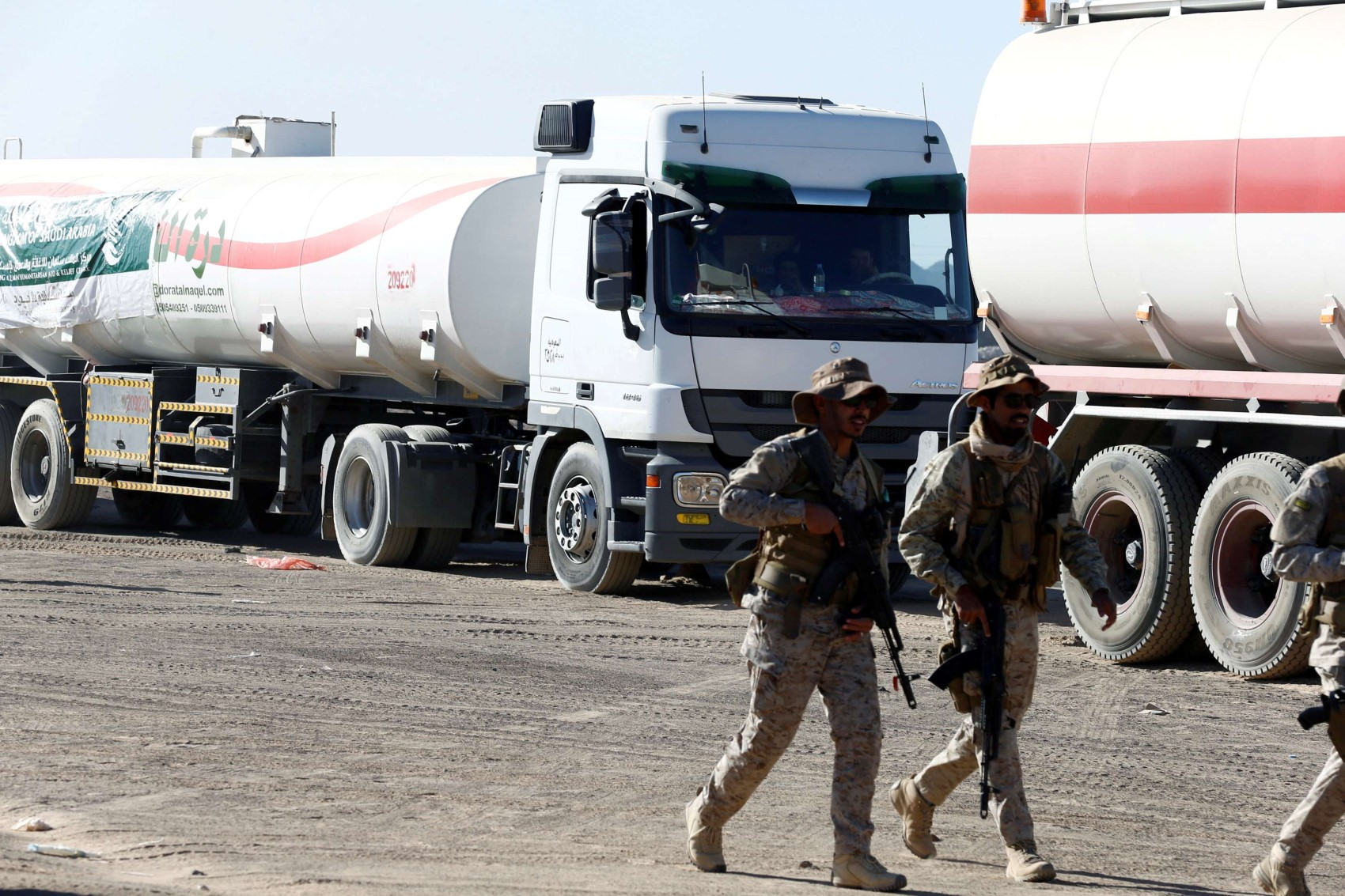 Saudi soldiers walk by oil tanker trucks delivered by Saudi authorities to support charities and NGOs in Marib, last January. (Reuters)