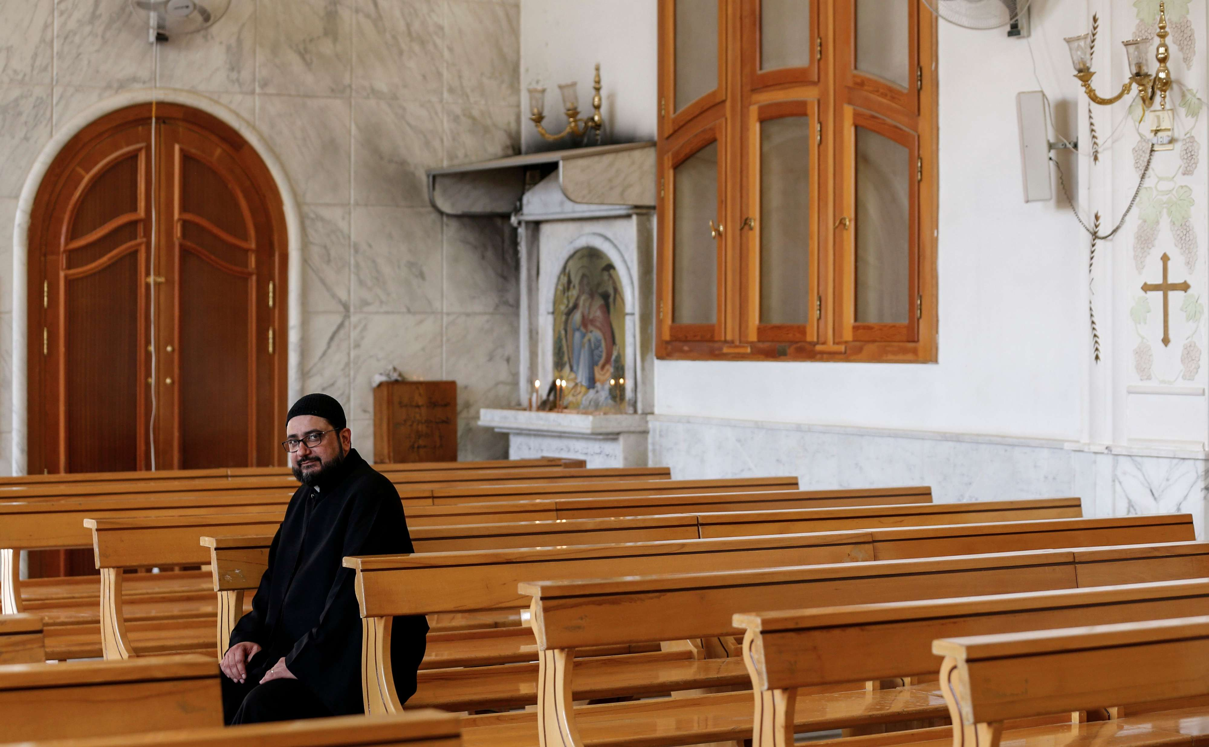 Lingering grievances. A parish priest sits on a bench in the St. Elias Syriac Orthodox church in the Syrian Christian village of Fairouzah. (AFP)
