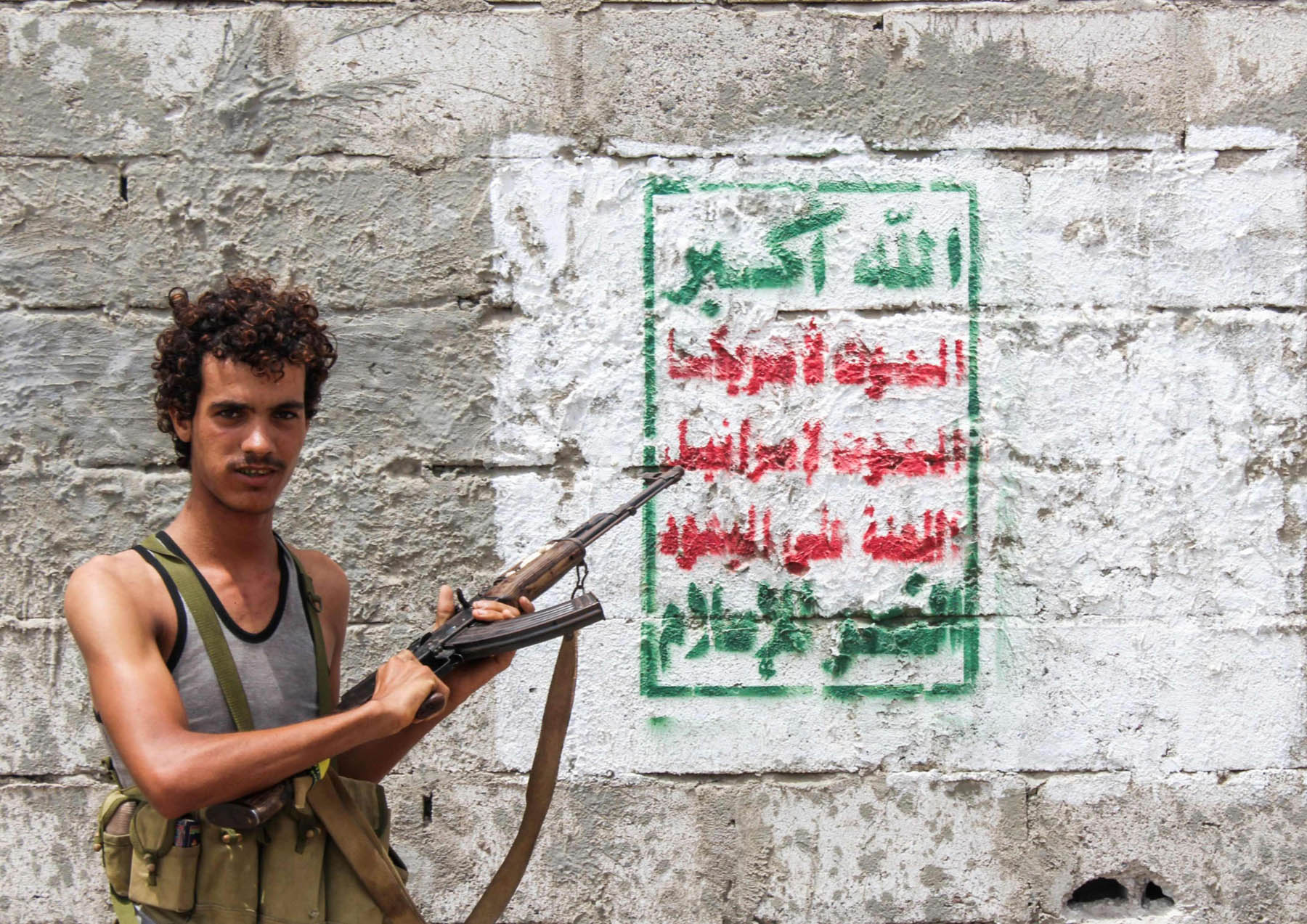 A pro-government fighter points a Kalashnikov assault rifle towards a Houthi banner painted on a wall on the southern outskirts of Hodeidah.    		              (AFP)