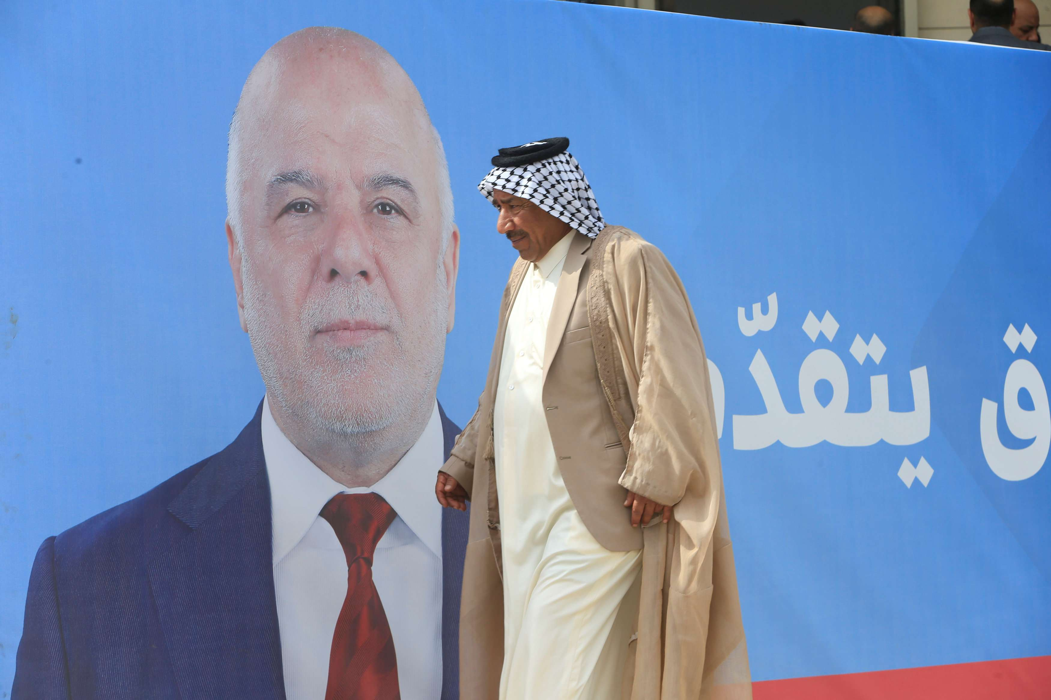 A man walks past a campaign poster of Iraqi Prime Minister Haider al-Abadi in Najaf.  (Reuters)