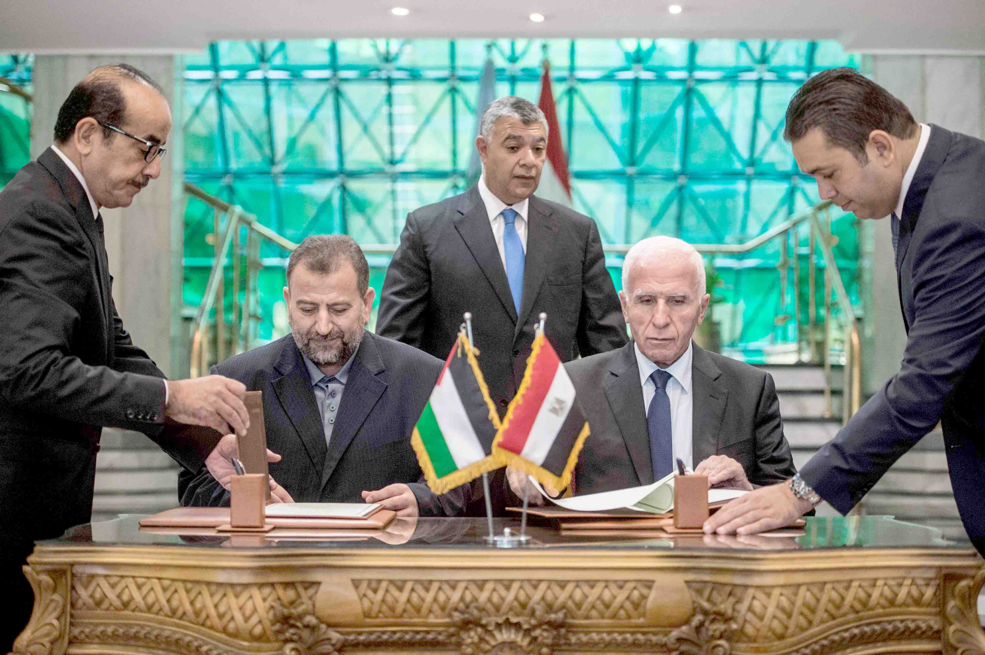A 2017 file picture shows Fatah's Azzam al-Ahmad (R) and Saleh al-Aruri (L) of Hamas signing a reconciliation deal at the Egyptian intelligence services headquarters in Cairo. (AFP)