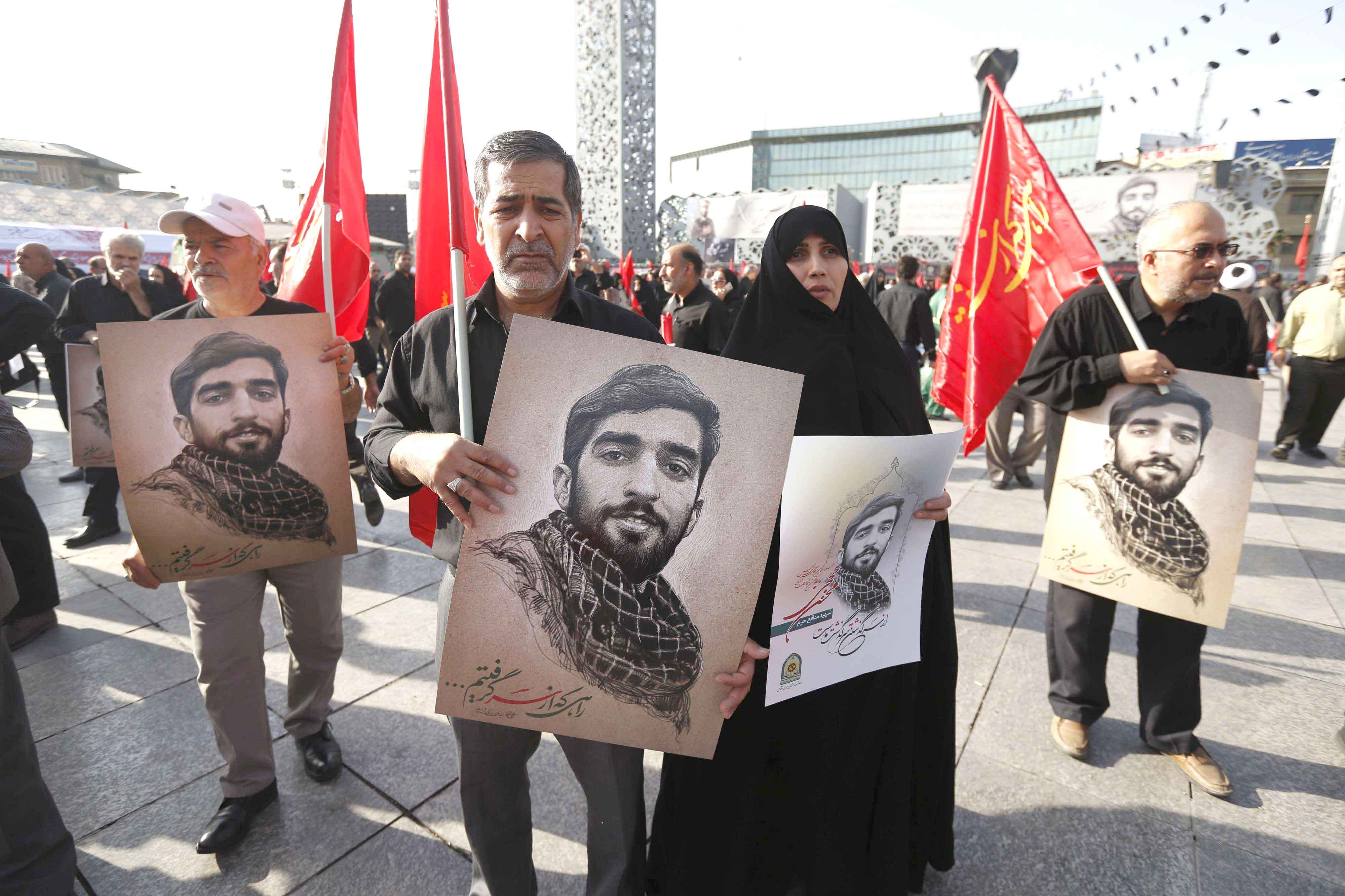 Iranian mourners hold portraits of a young member of Iran's Islamic Revolutionary Guard Corps (IRGC) who was killed in Syria. (AFP)