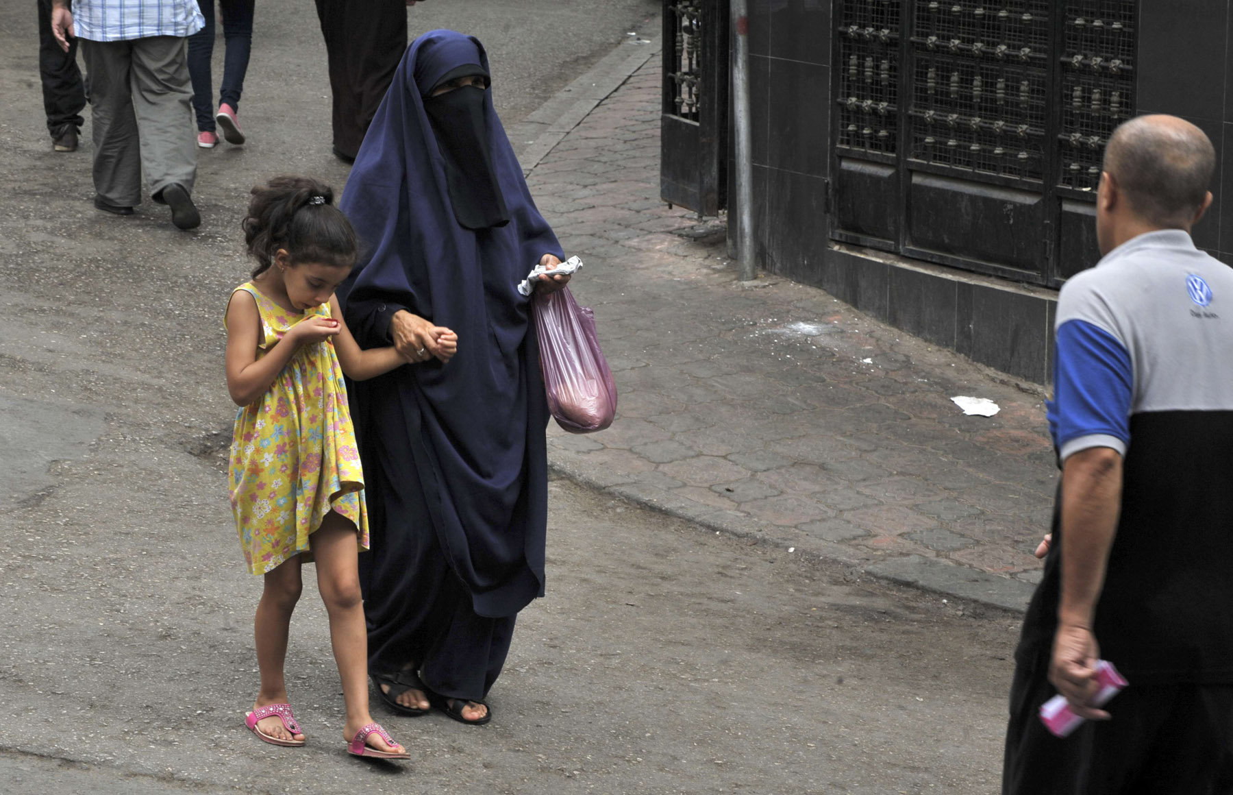 A veiled woman walks with a girl in central Algiers. (AFP)
