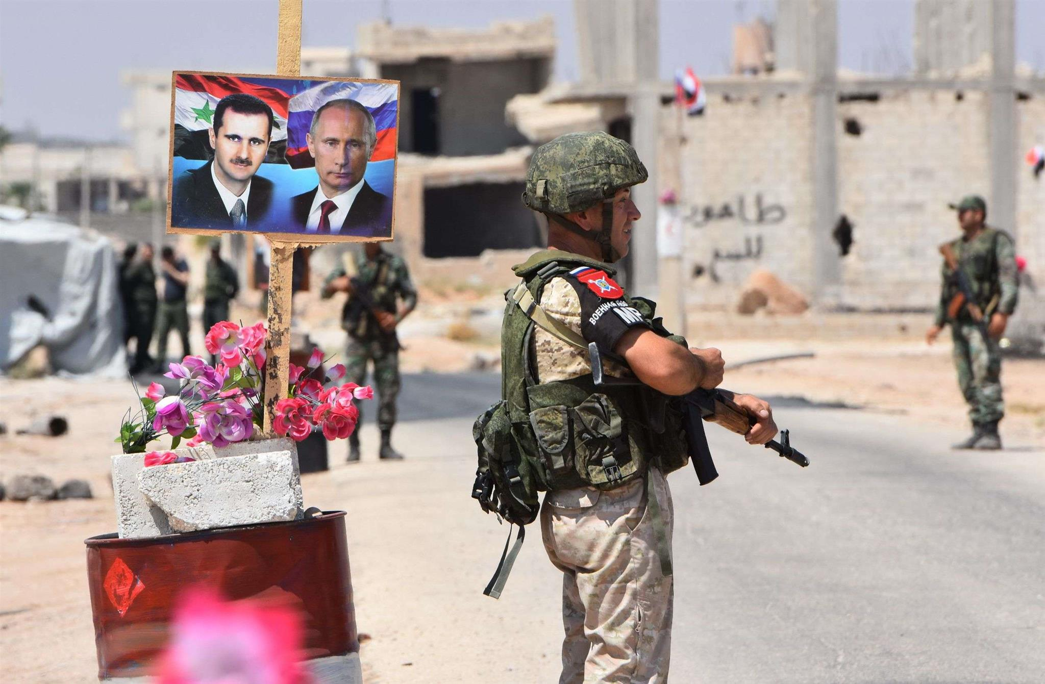 Members of Russian and Syrian forces stand guard near posters of Syrian President Bashar Assad (L) and his Russian counterpart Vladimir Putin at the Abu Duhur crossing on the eastern edge of Idlib, last August.(AFP)