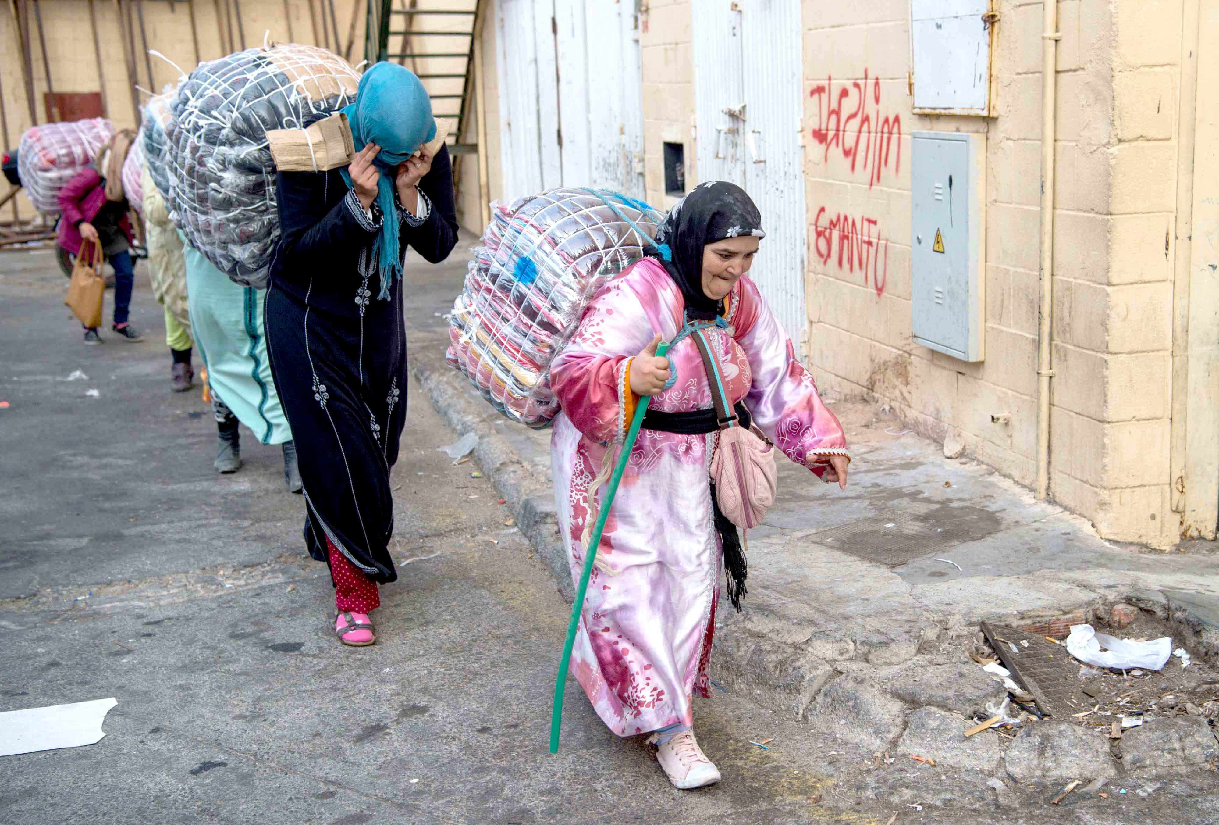 Moroccan women porters carry bundles of goods on their backs on their way from the Spanish exclave of Ceuta to Morocco, on September 20. (AFP)
