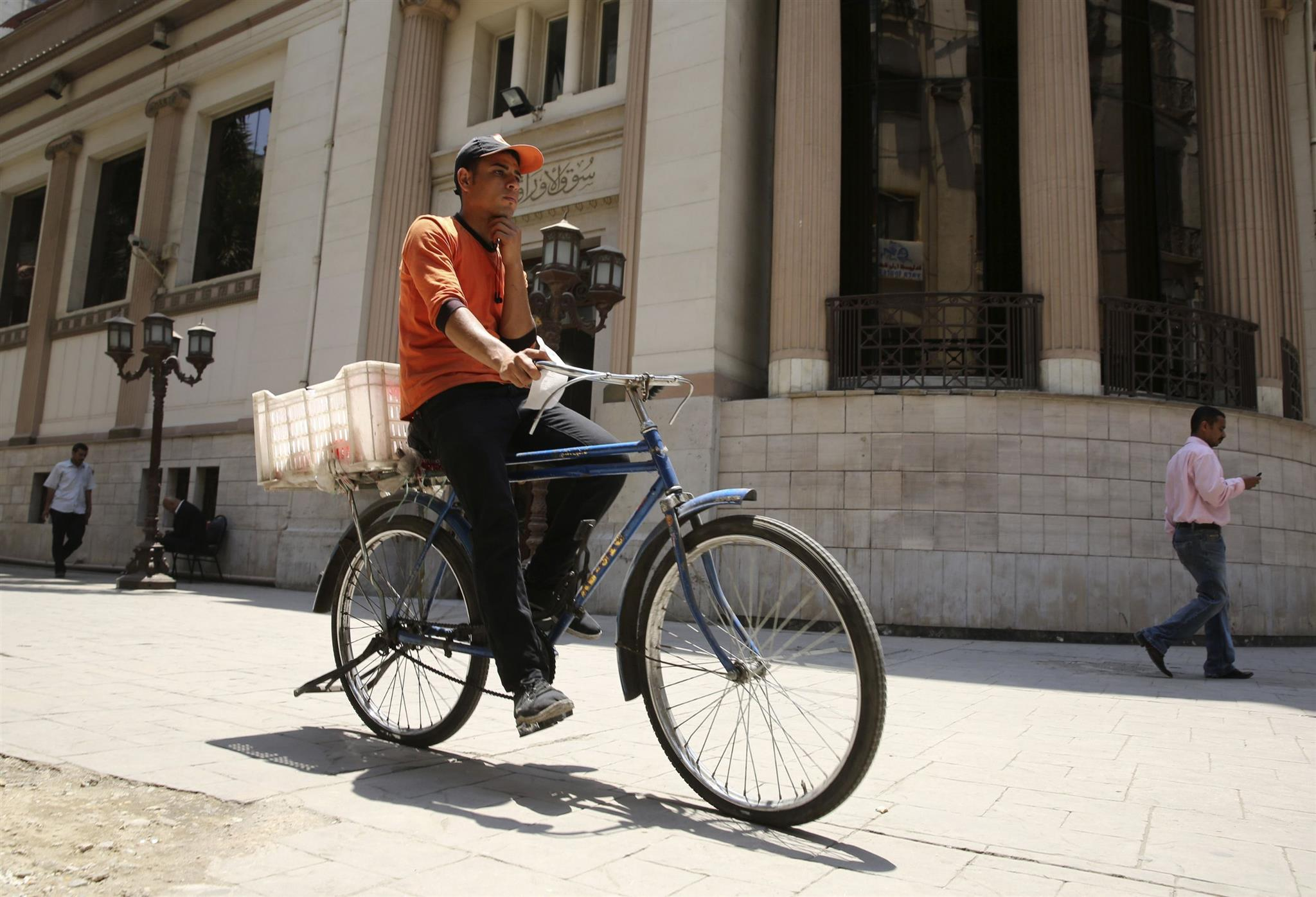 A man rides a bicycle in front of the Egyptian Stock Exchange in Cairo. (Reuters)