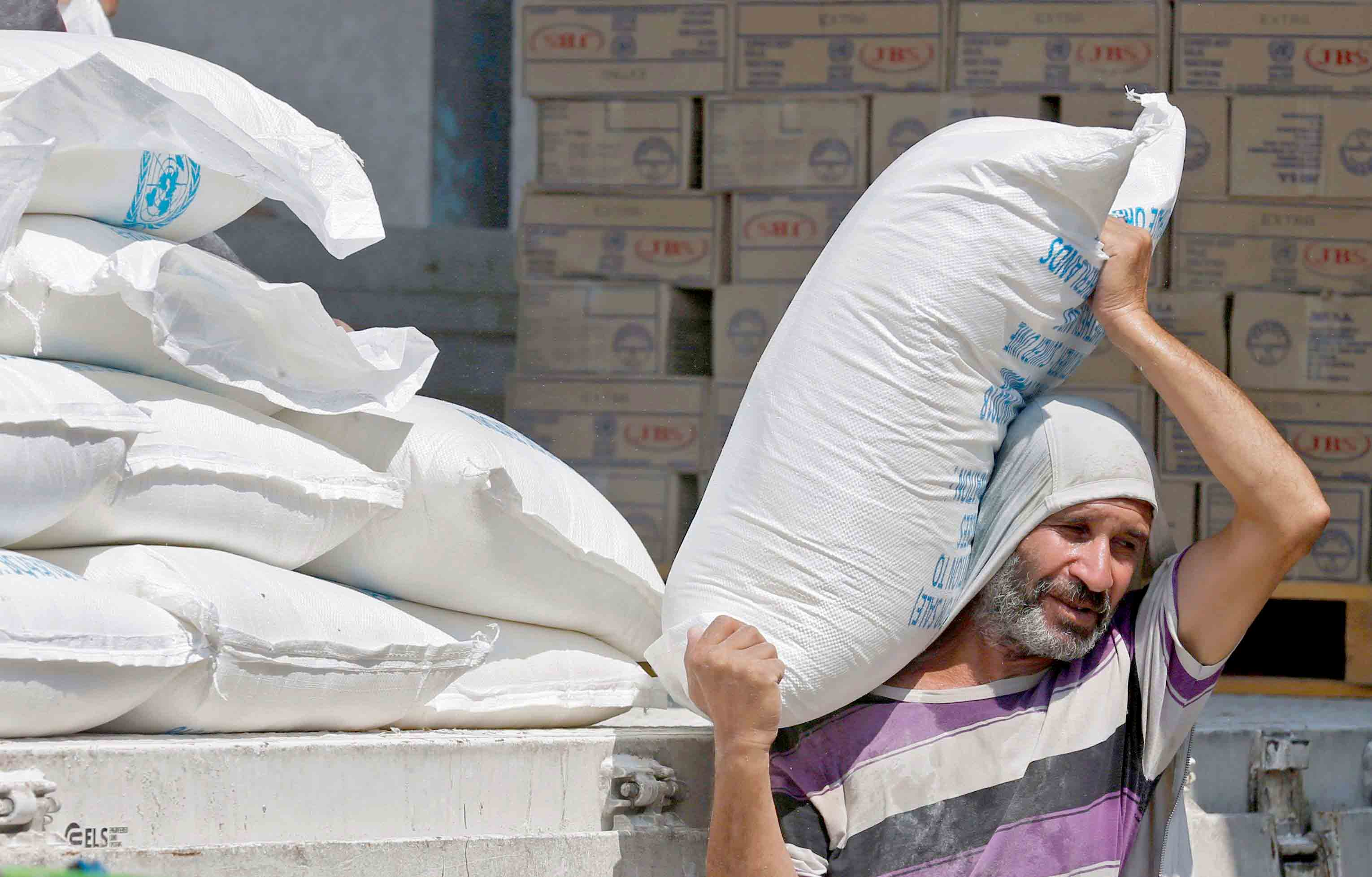 Increasingly vulnerable. A Palestinian man carries a bag of flour outside an UNRWA aid distribution centre in Khan Younis, on September 4.(AFP)