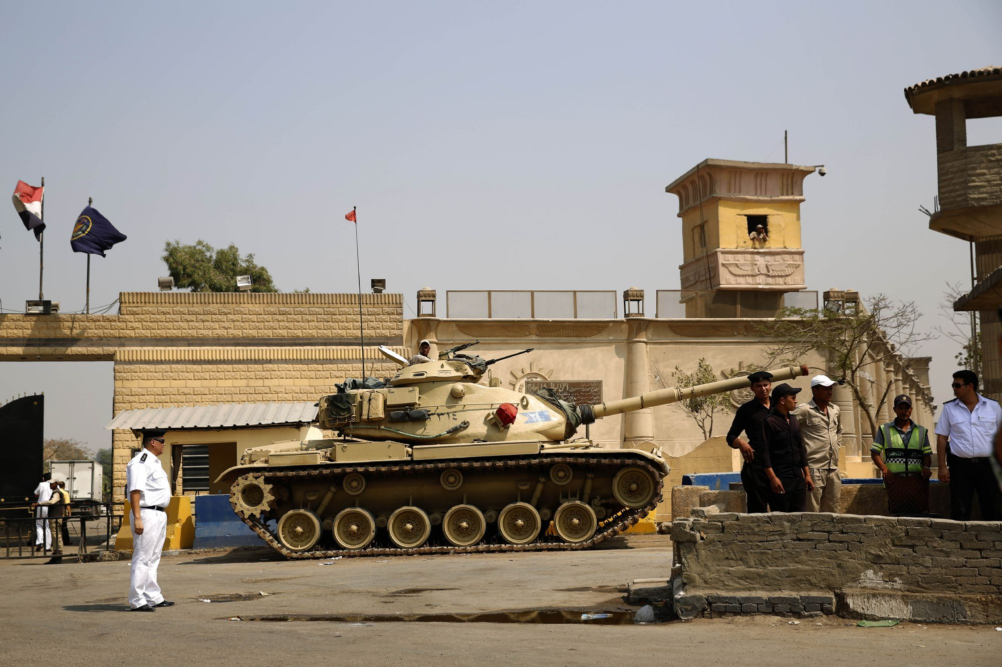 Numbers up, costs up.  Egyptian security stand guard outside one of the entrances of Tora prison in Cairo. (AP)