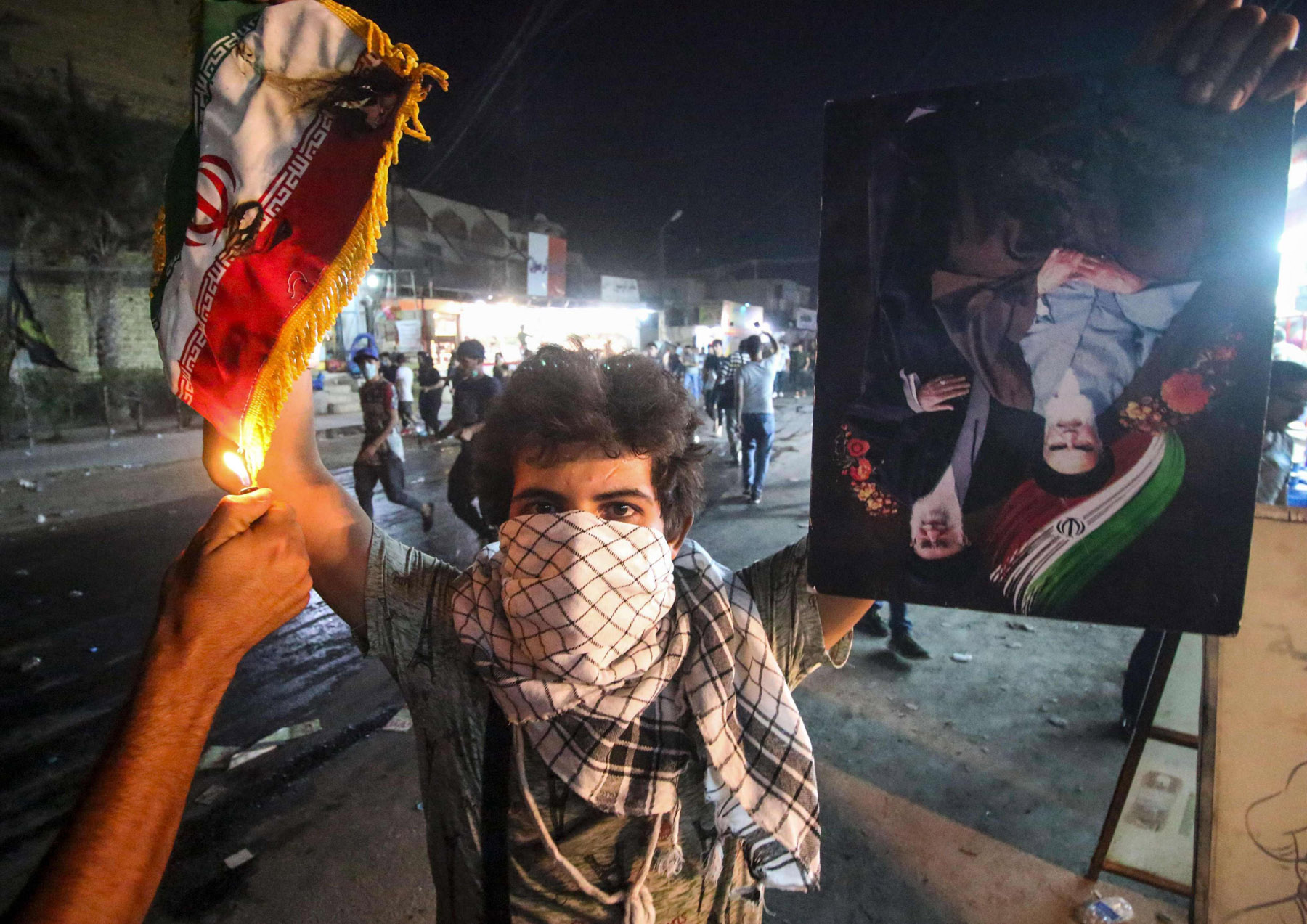 An Iraqi protester holds up an Iranian flag as another lights it up during protests in Basra, on September 7.  (AFP)
