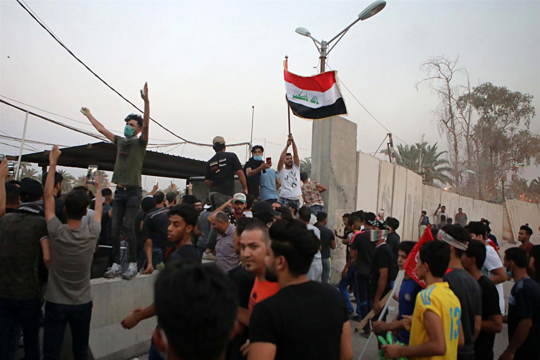 Protesters raise the Iraqi flag at the gate of the Iranian Consulate building before storming it in Basra, on September 7.                                                  (AP)