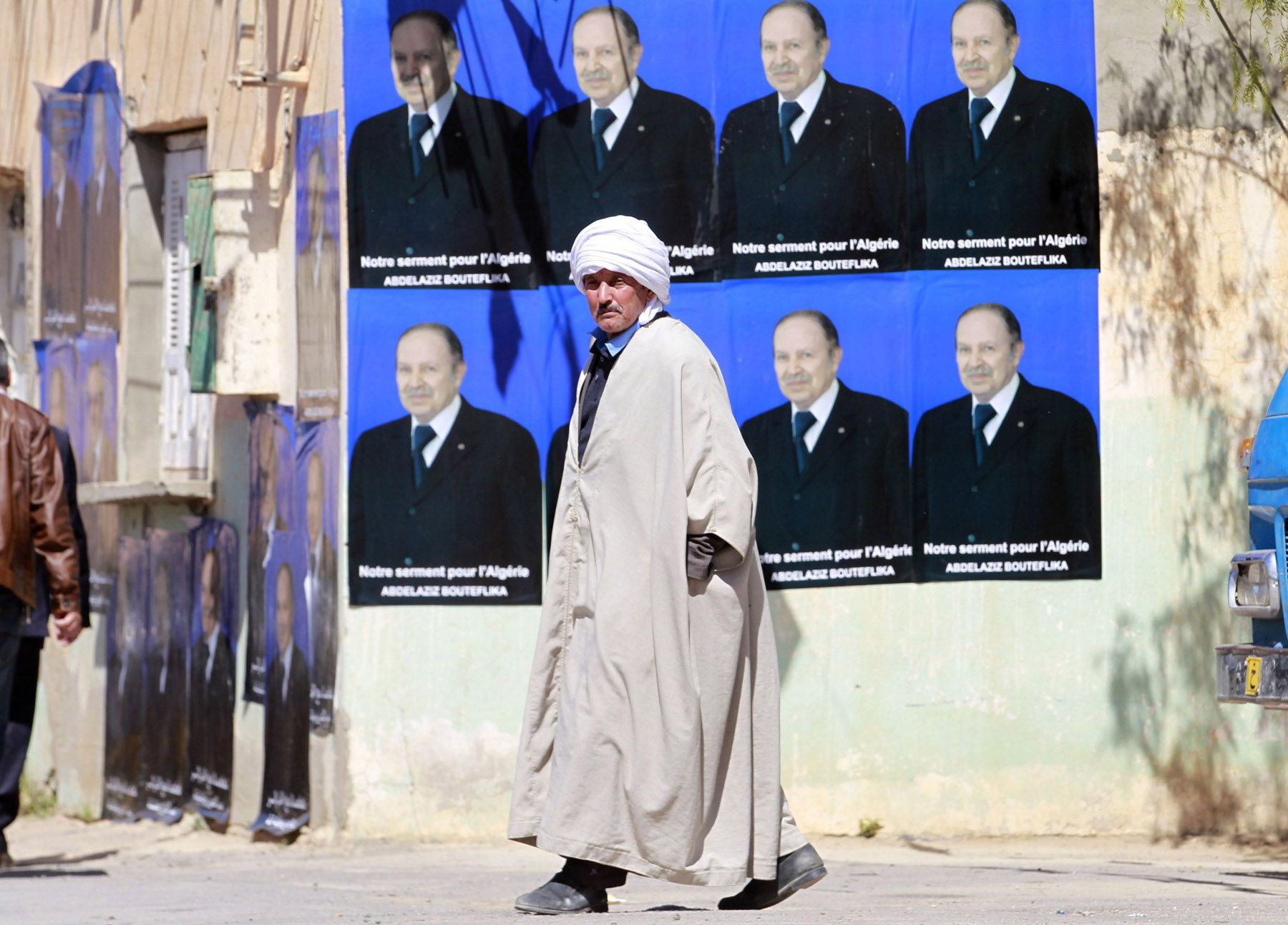 At crossroads. A man walks past posters of Algerian President Abdelaziz Bouteflika in Ain Ouassara, south-west of Algiers. (Reuters)