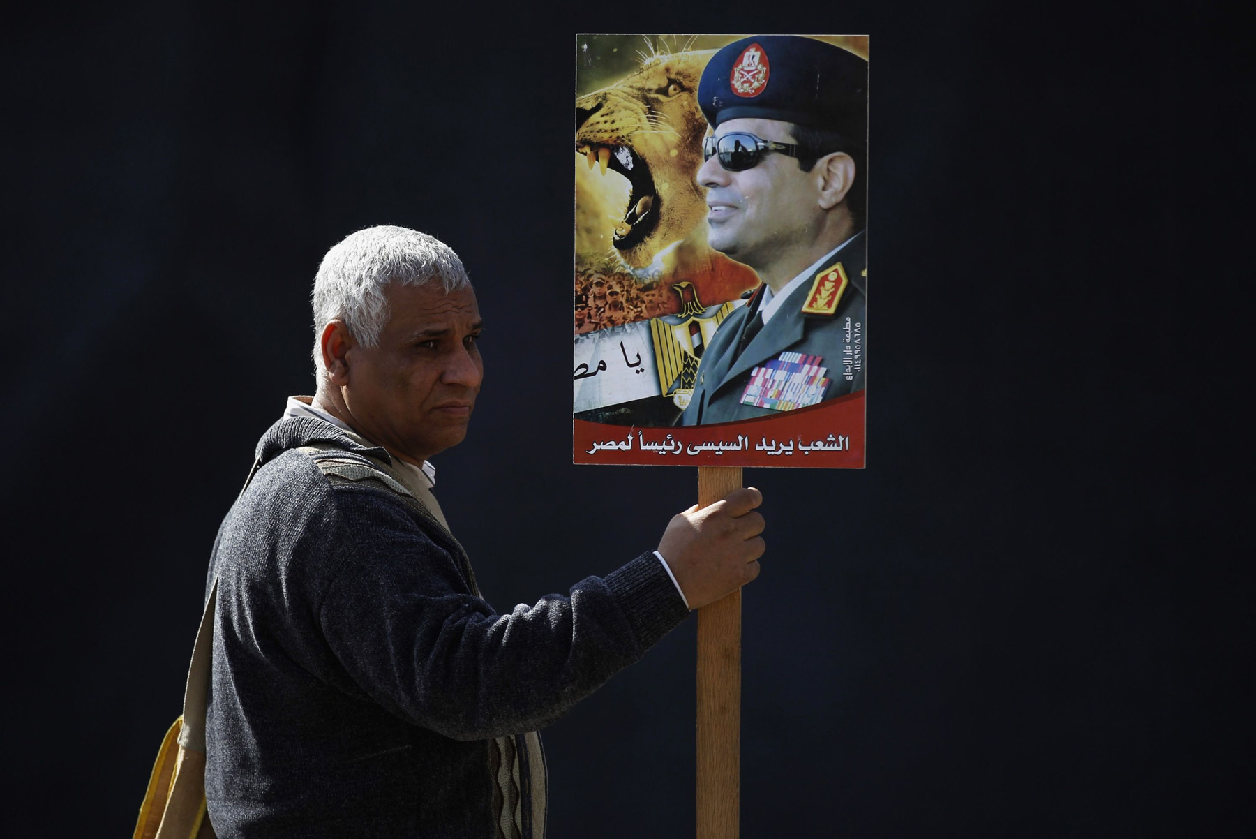 An Egyptian man holds a poster of Egyptian President Abdel Fattah al-Sisi near the presidential palace in Cairo.  (Reuters)