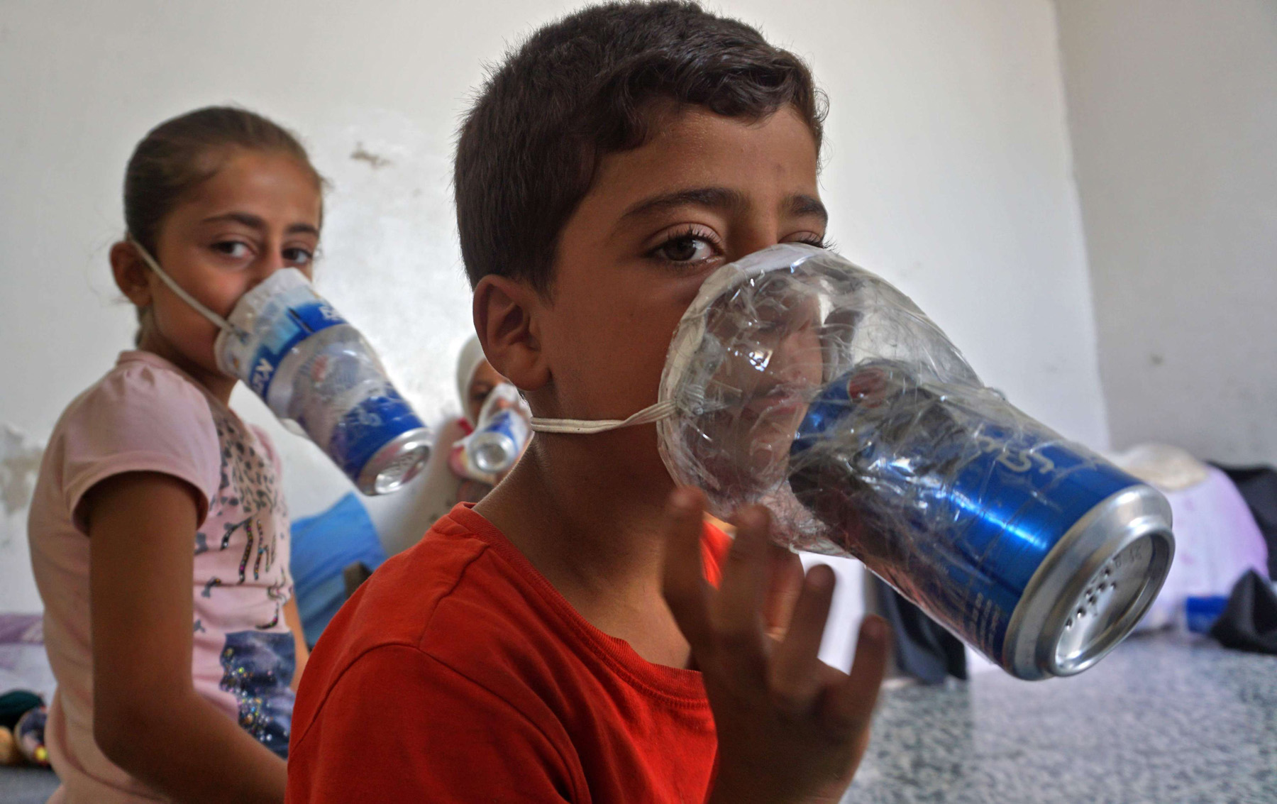 Children try improvised gas masks in their home in northern Idlib province, on September 12. (AFP)