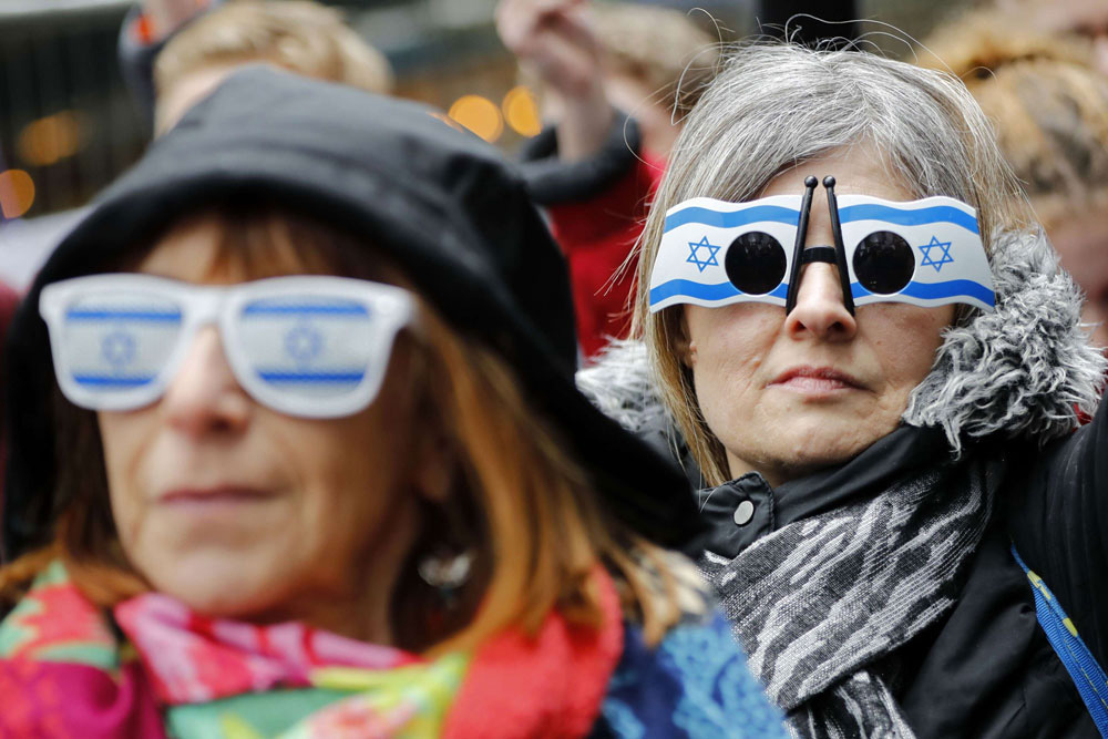 People wear flag of Israel glasses at a gathering organised by the Campaign Against Antisemitism outside the head office of the British opposition Labour Party in London.       (AFP)