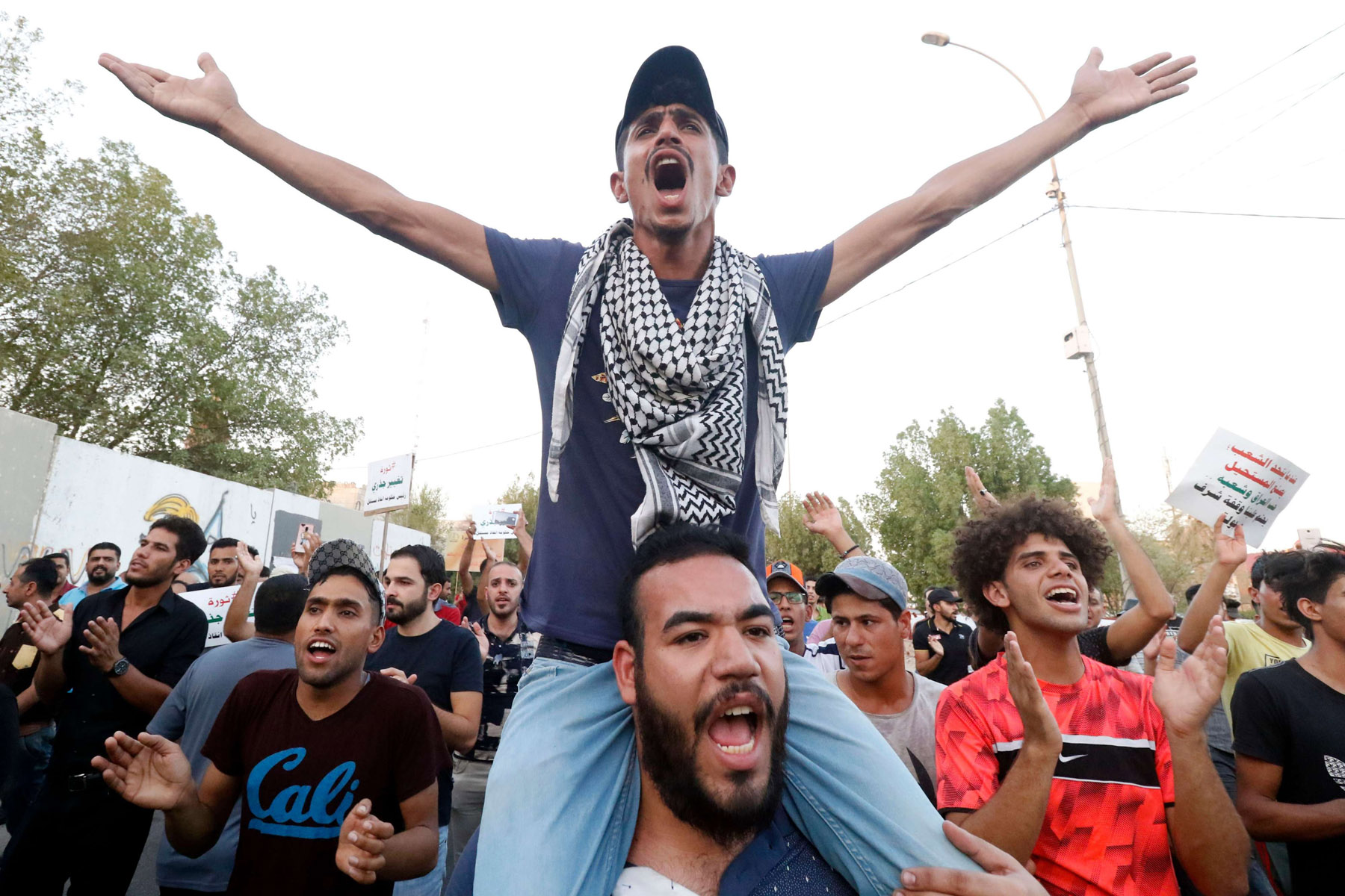 Fed up. Iraqis shout slogans during ongoing protests in the southern city of Basra, on August 24. 									    (AFP)