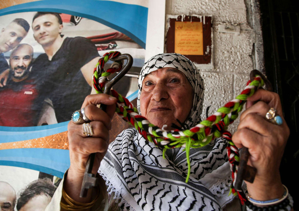 A Palestinian woman holds the key of her family's home as she sits at the Balatah refugee camp in the occupied West Bank, on September 2. (AFP)