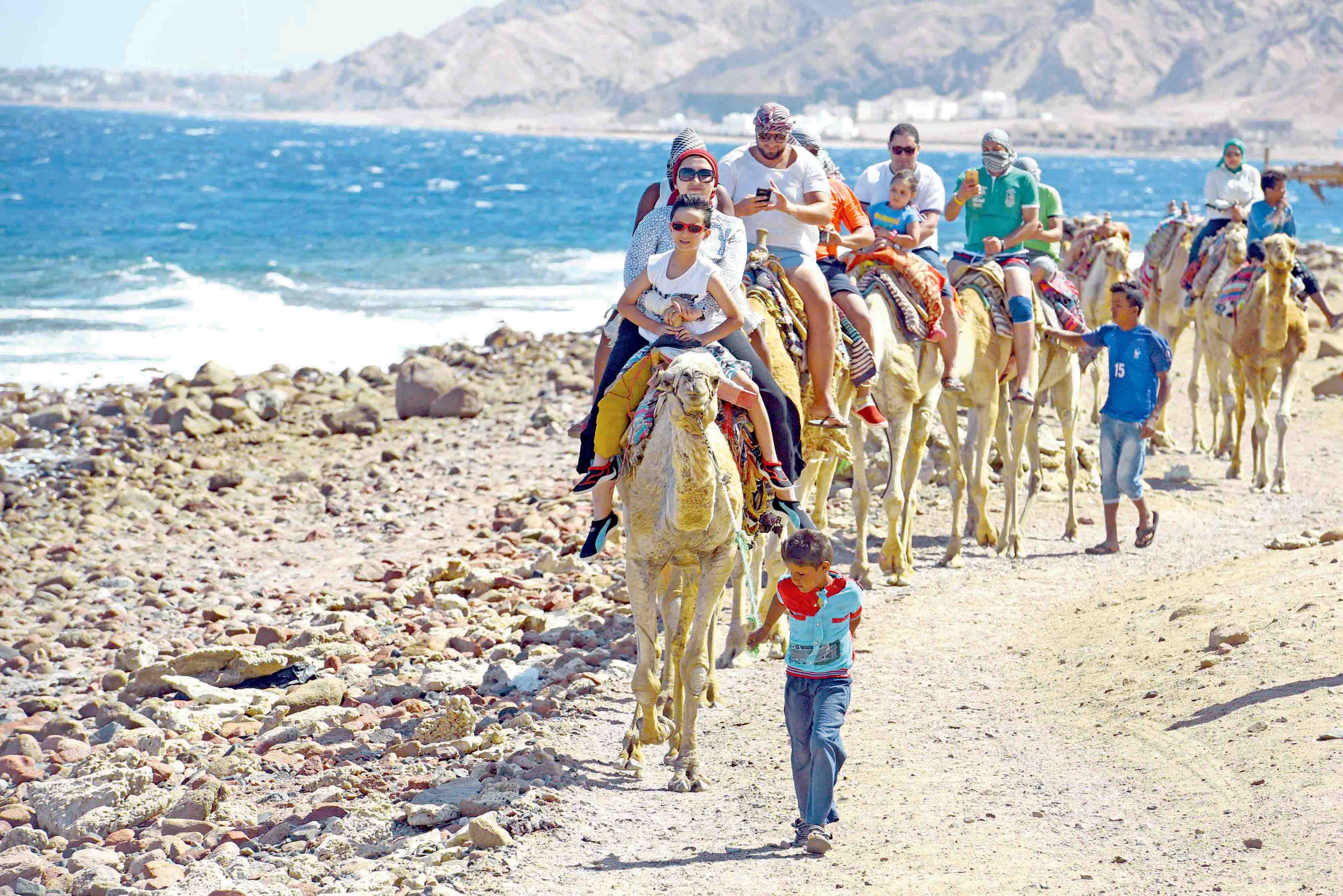 Tourists ride camels on the shores of the town of Dahab, in Egypt's southern Sinai Peninsula.(AFP)