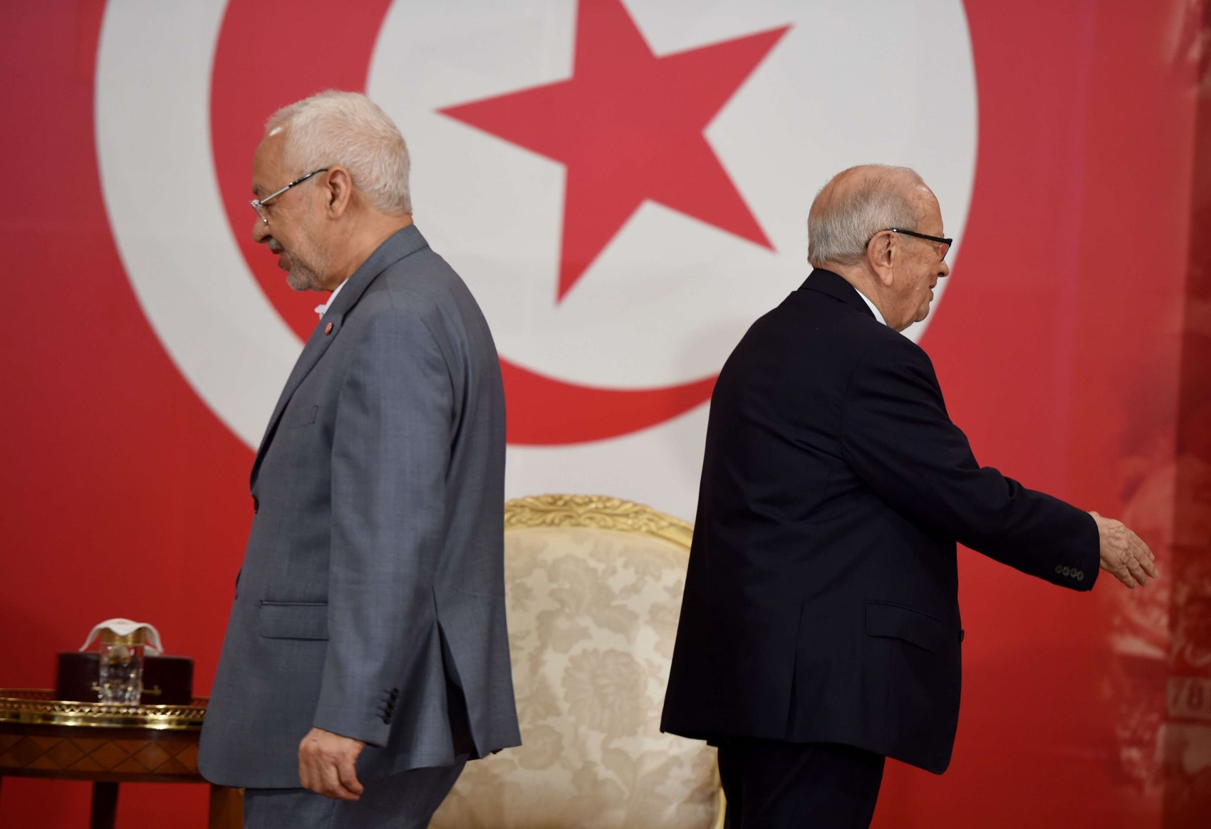 A picture dated on July 13, 2016 shows Tunisian President Beji Caid Essebsi (R) walking the opposite direction from the leader of the Islamist Ennahdha party, Rached Ghannouchi. (AFP)