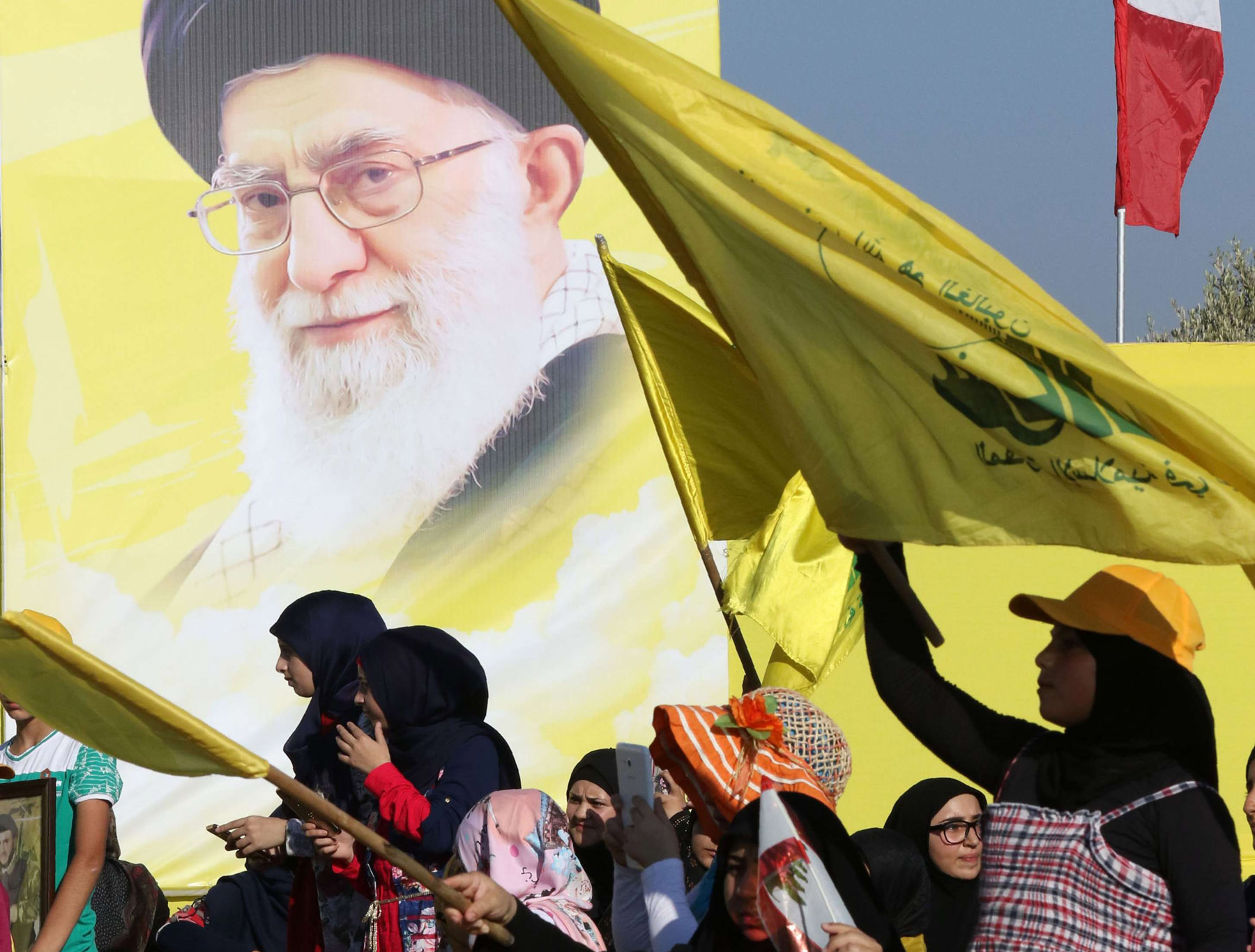 Lebanese women wave a national flag and Shia movement Hezbollah flags in front of a portrait of Iran's supreme Leader Ayatollah Ali Khamenei, in Bint Jbeil in southern Lebanon. (AFP)