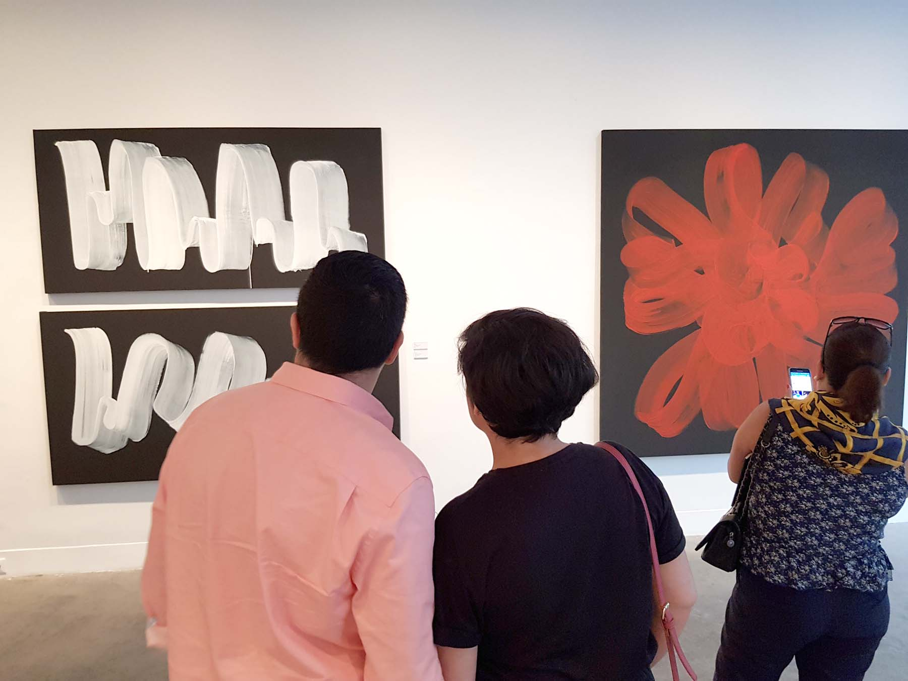Visitors look at paintings at L'Atelier 21 gallery in Casablanca. (Saad Guerraoui)