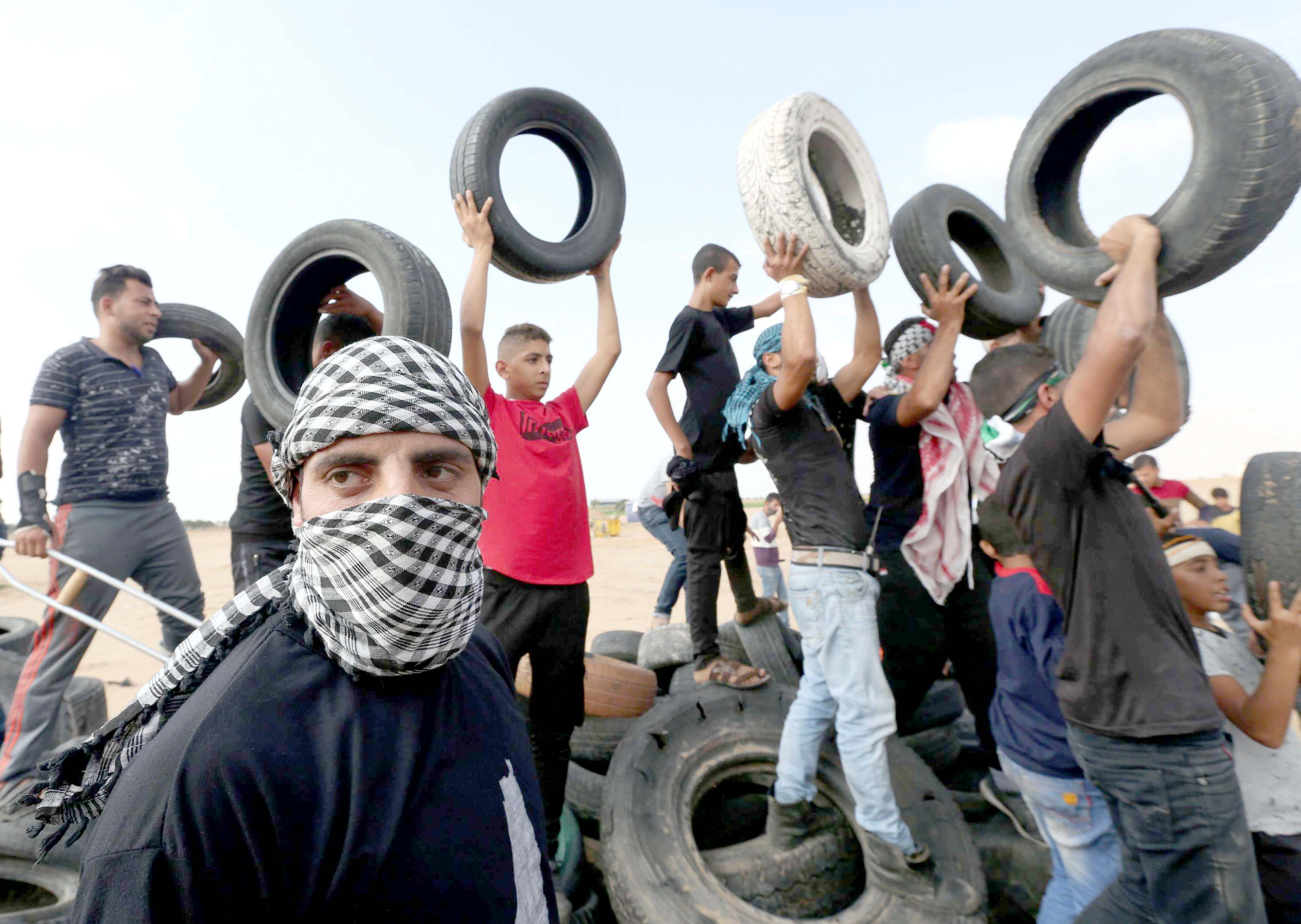 The next fire. Palestinian demonstrators hold tyres during a protest at the border fence in southern Gaza, on October 19.  (Reuters)