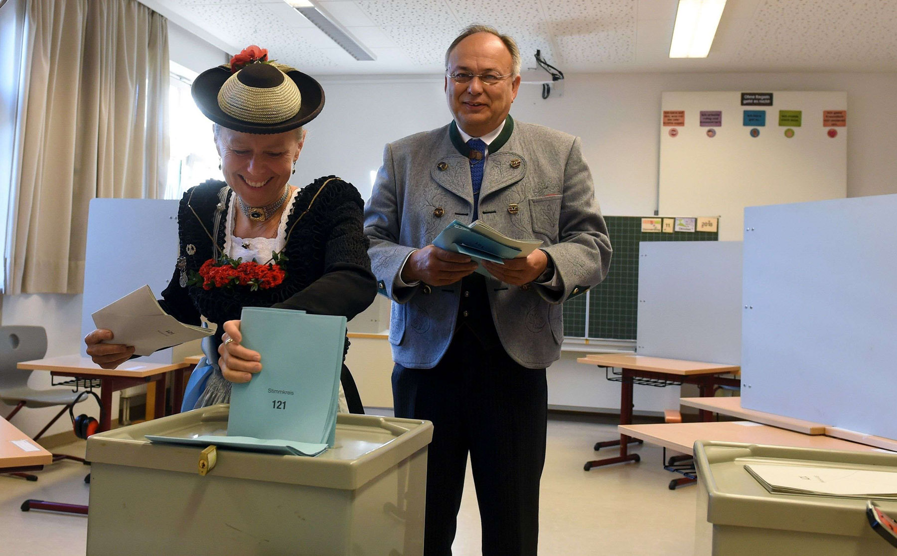 People dressed in traditional Bavarian clothes cast their votes for regional elections at a polling station in Neukirchen in southern Germany, on October 14.  (AFP)
