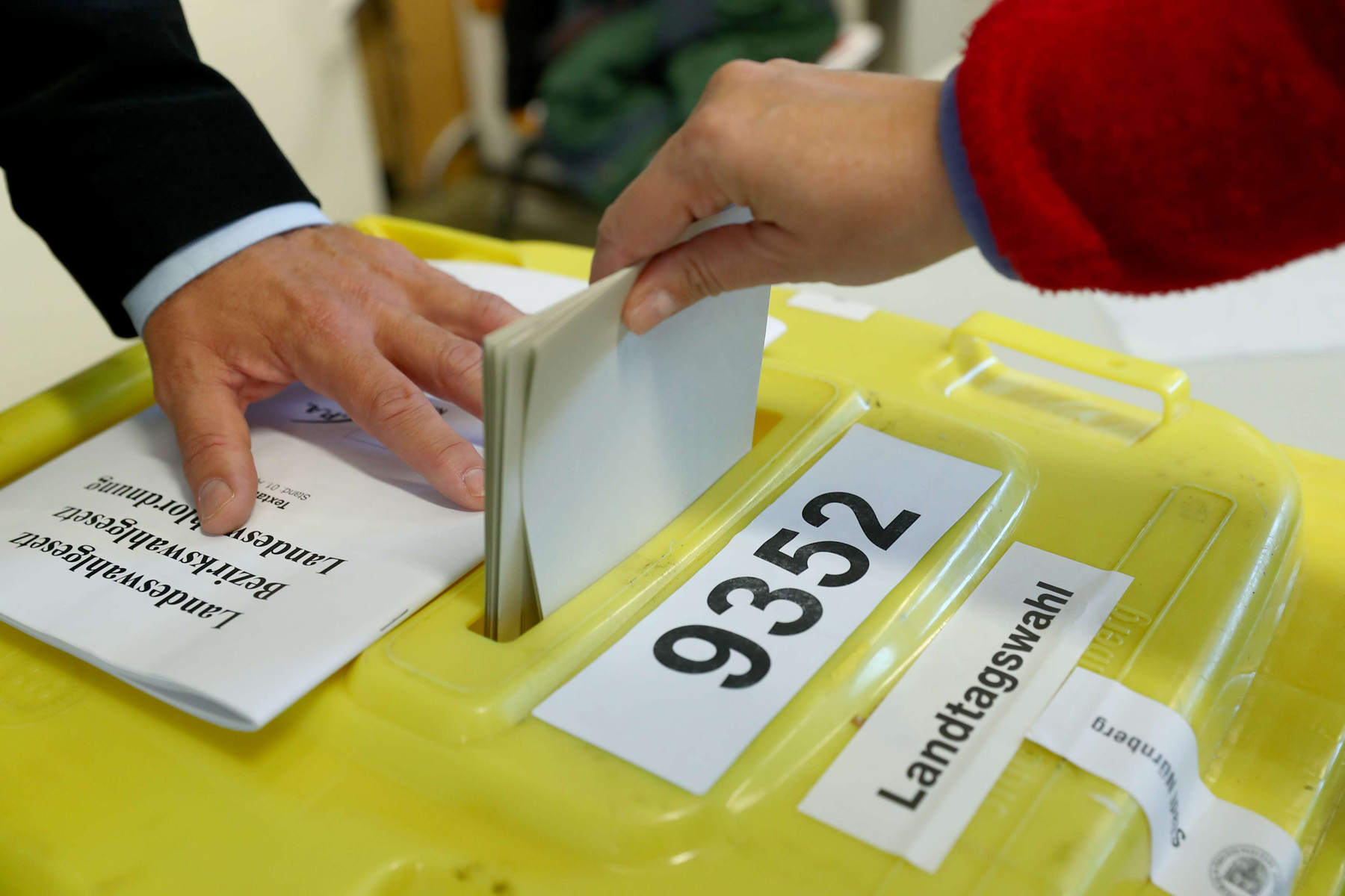 Not many dividends.  A voter casts her vote inside a ballot box at a polling station during the Bavaria state election, on 14 October.  (Daniel Karmann)