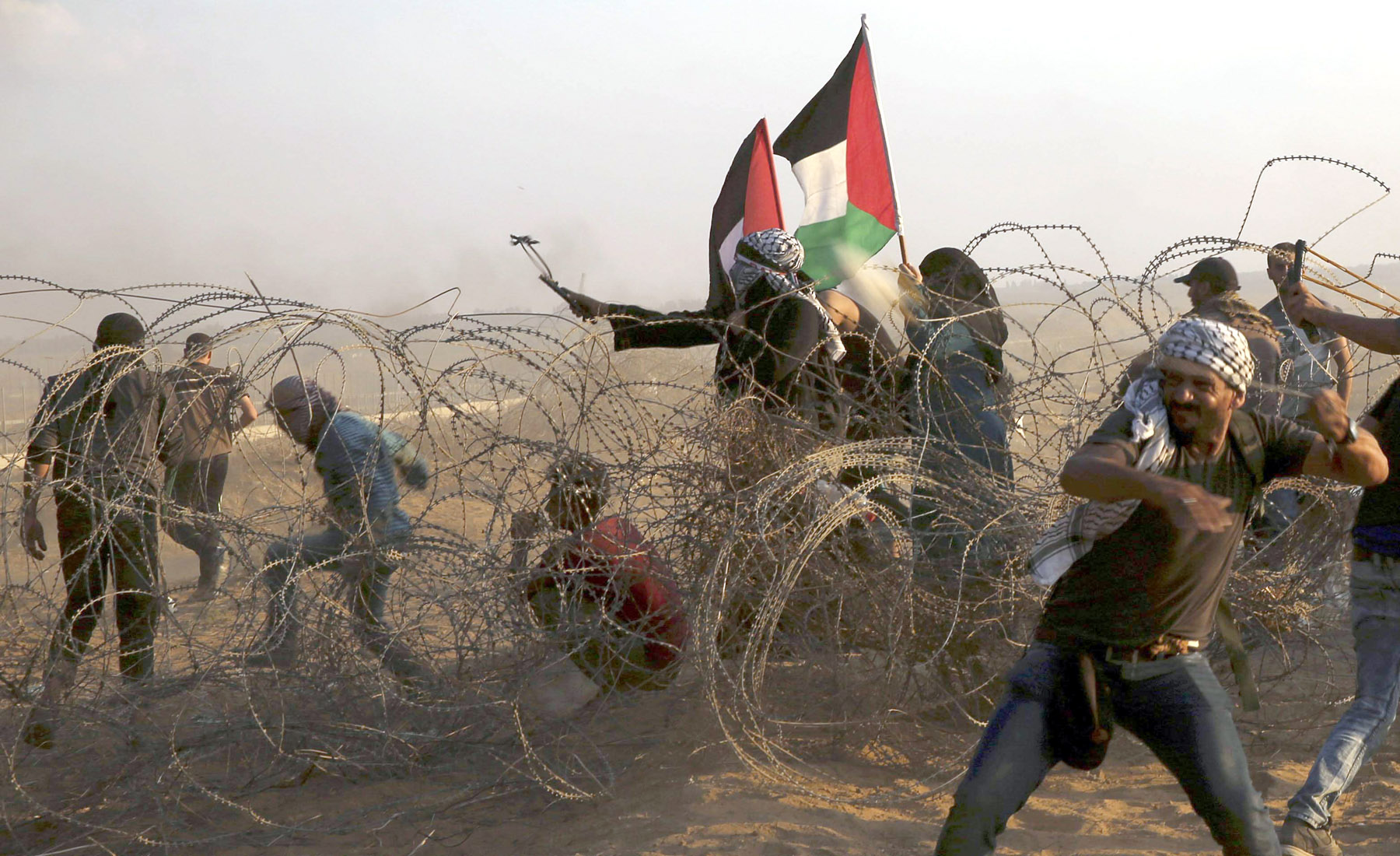 A protester uses a slingshot to hurl stones while others throw stones near the fence of the Gaza Strip border with Israel, on October 12.              (AP)