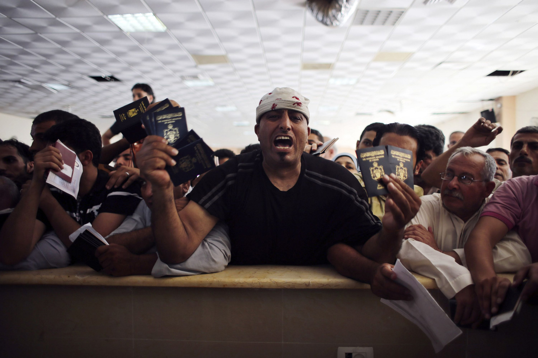 A Palestnian man, who is hoping to cross into Egypt, shouts as he holds his passport and other family members' passports at the Rafah border crossing. (Reuters)