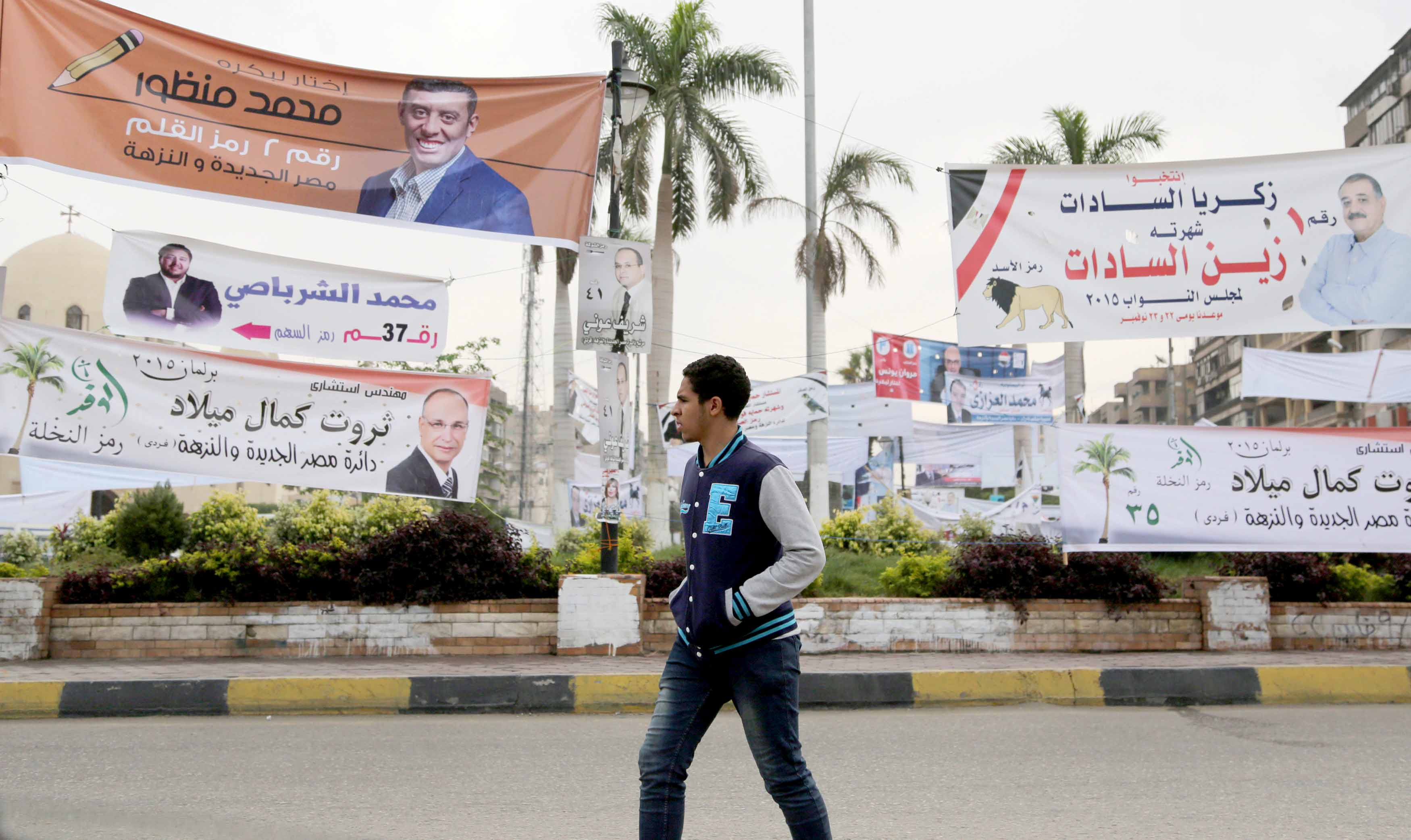 A 2015 file picture shows a young man walking past electoral banners in the Heliopolis area. (Reuters)