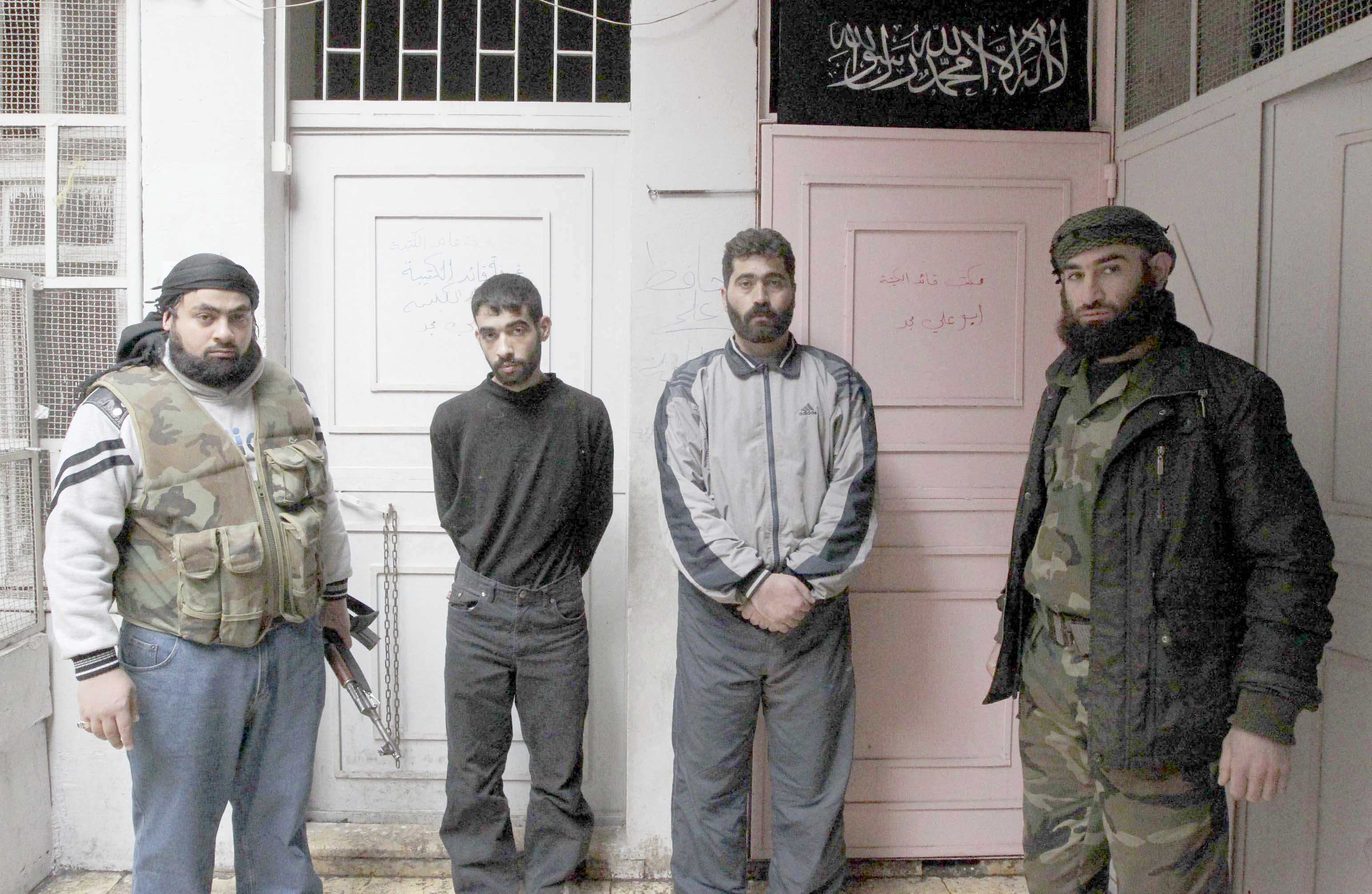 Shadowy villains. A 2013 file picture shows Syrian rebels standing next to two detainees (2nd L, 2nd R) of shabbiha in Aleppo. (Reuters)