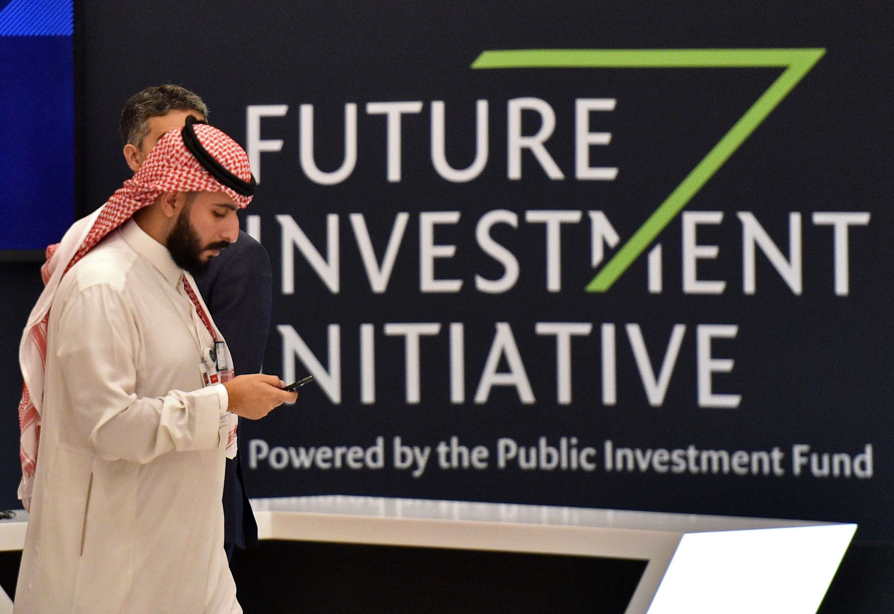A Saudi man walks past a sign at the start of the Future Investment Initiative (FII) in Riyadh, on October 23. (AFP)