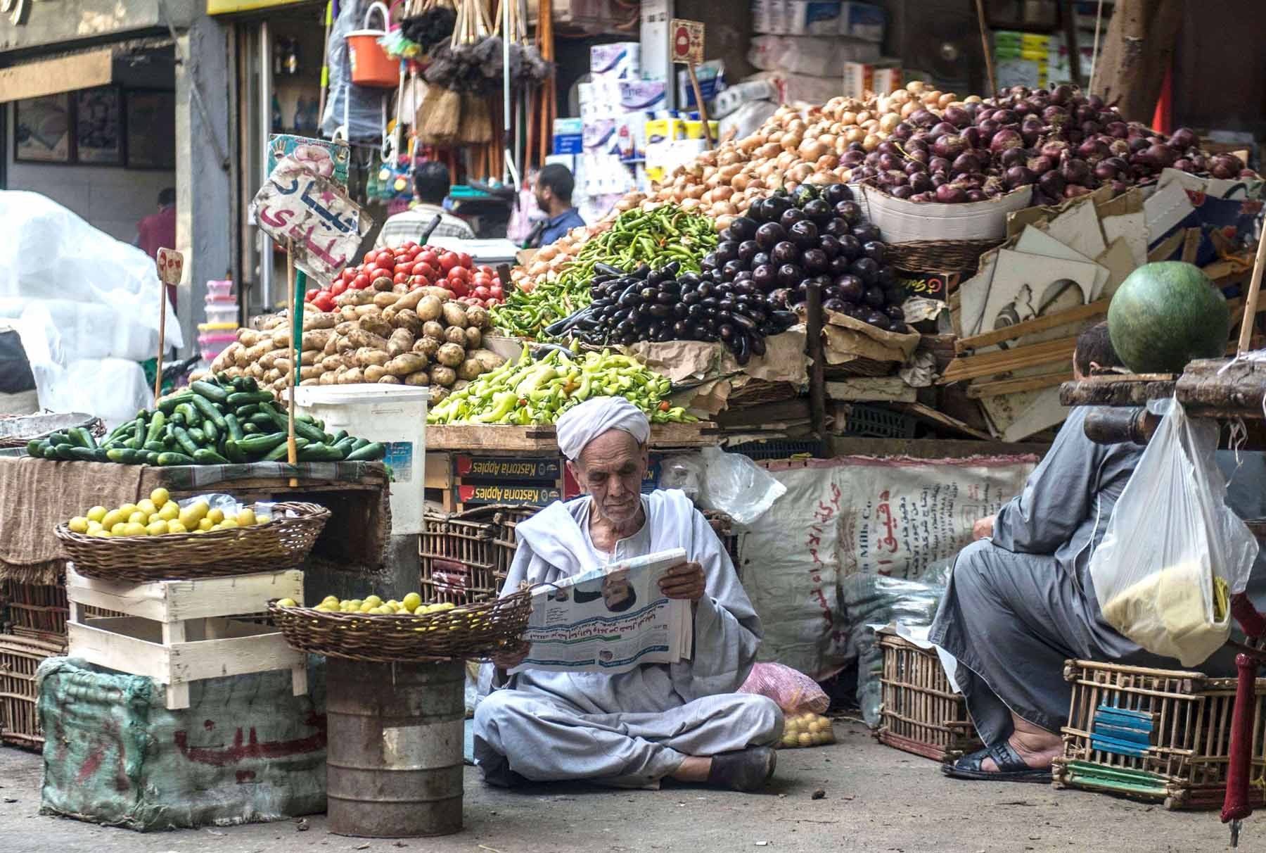 Subliminal news. An Egyptian vendor reads a newspaper outside his fruit and vegetable stand in  Cairo.    (AFP)