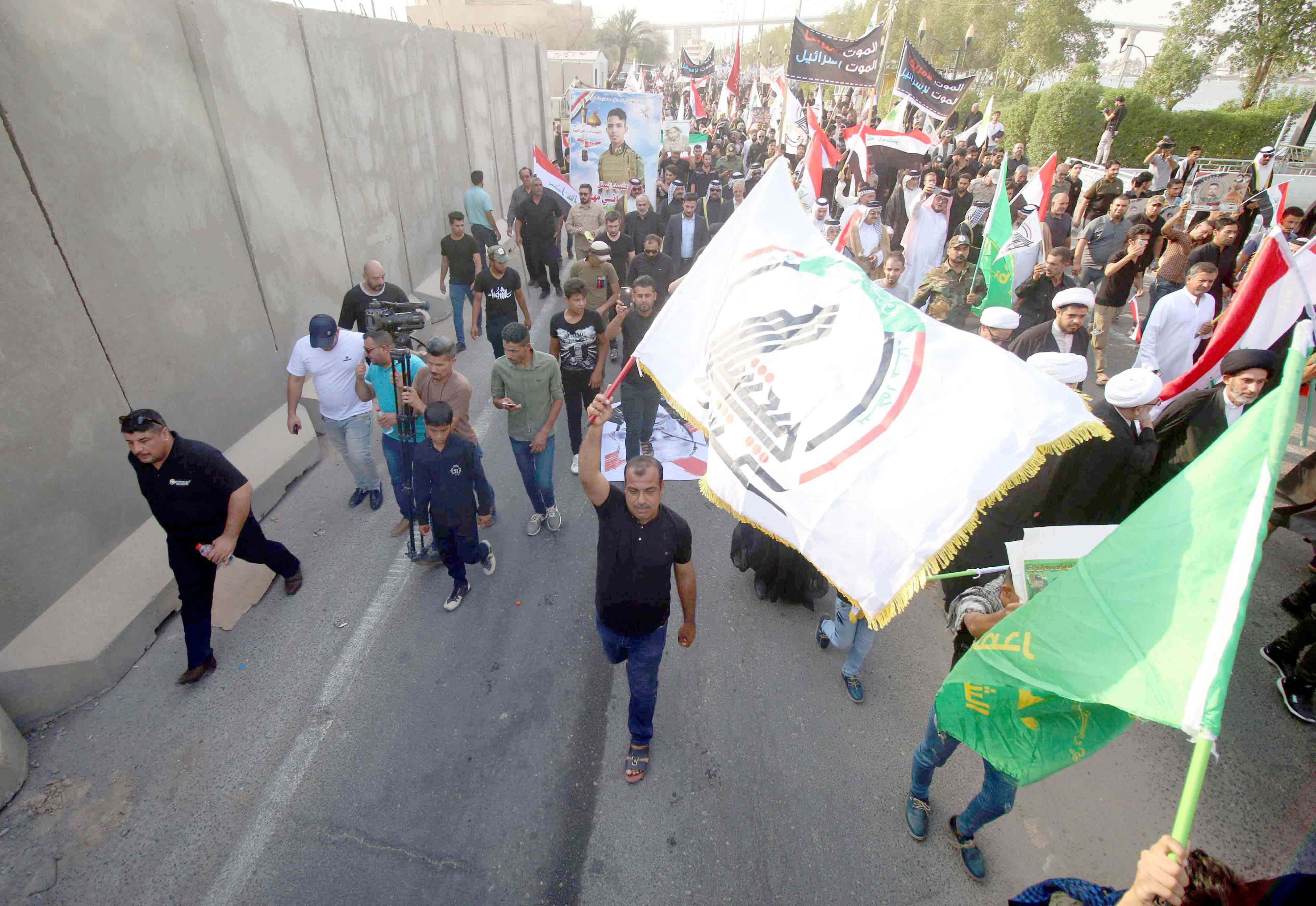 Iraqi Shia demonstrators wave Iranian and pro-Iranian party flags during a protest in Basra, on September 15. (AFP)