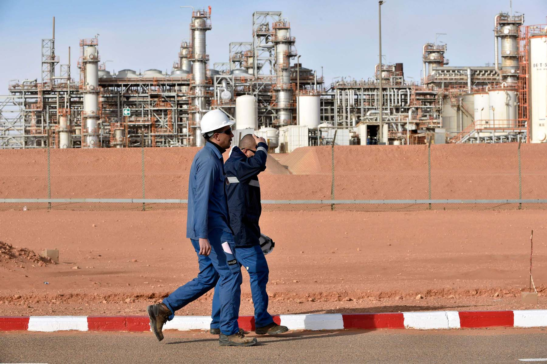 Workers walk past the In Amenas gas plant  south-east of Algiers. (AFP)
