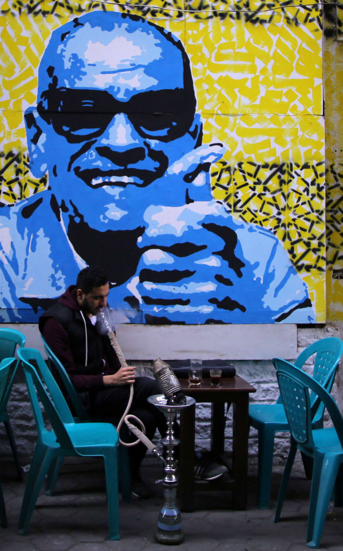 Reconciling differences. An Egyptian man smokes a water pipe in front of a mural of Egyptian novelist Naguib Mahfouz in Cairo.   (Reuters)