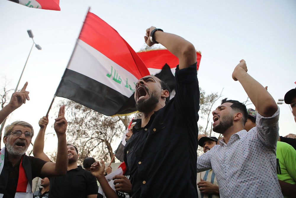 Iraqi protesters wave national flags and chant slogans during a demonstration demanding better public services and jobs in the southern city of Basra, last September. (AP)
