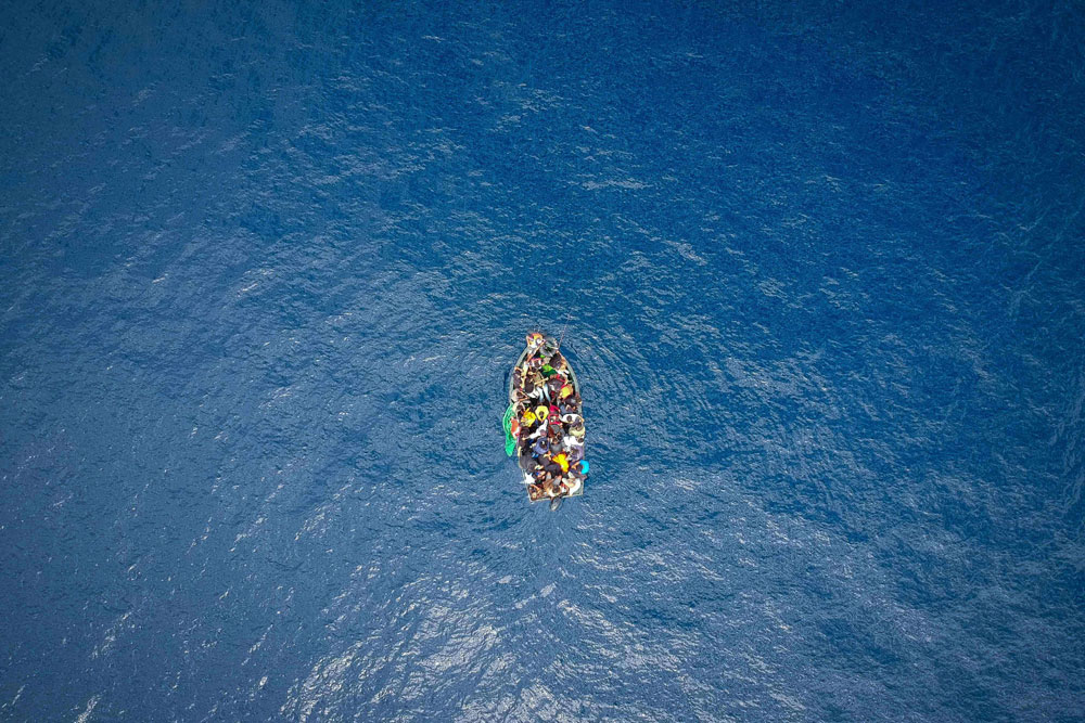 An aerial photo shows a boat carrying migrants stranded in the Strait of Gibraltar before being rescued by the Spanish Guardia Civil and the Salvamento Maritimo sea search and rescue agency that saw 157 migrants rescued on September 8, 2018. (AFP)